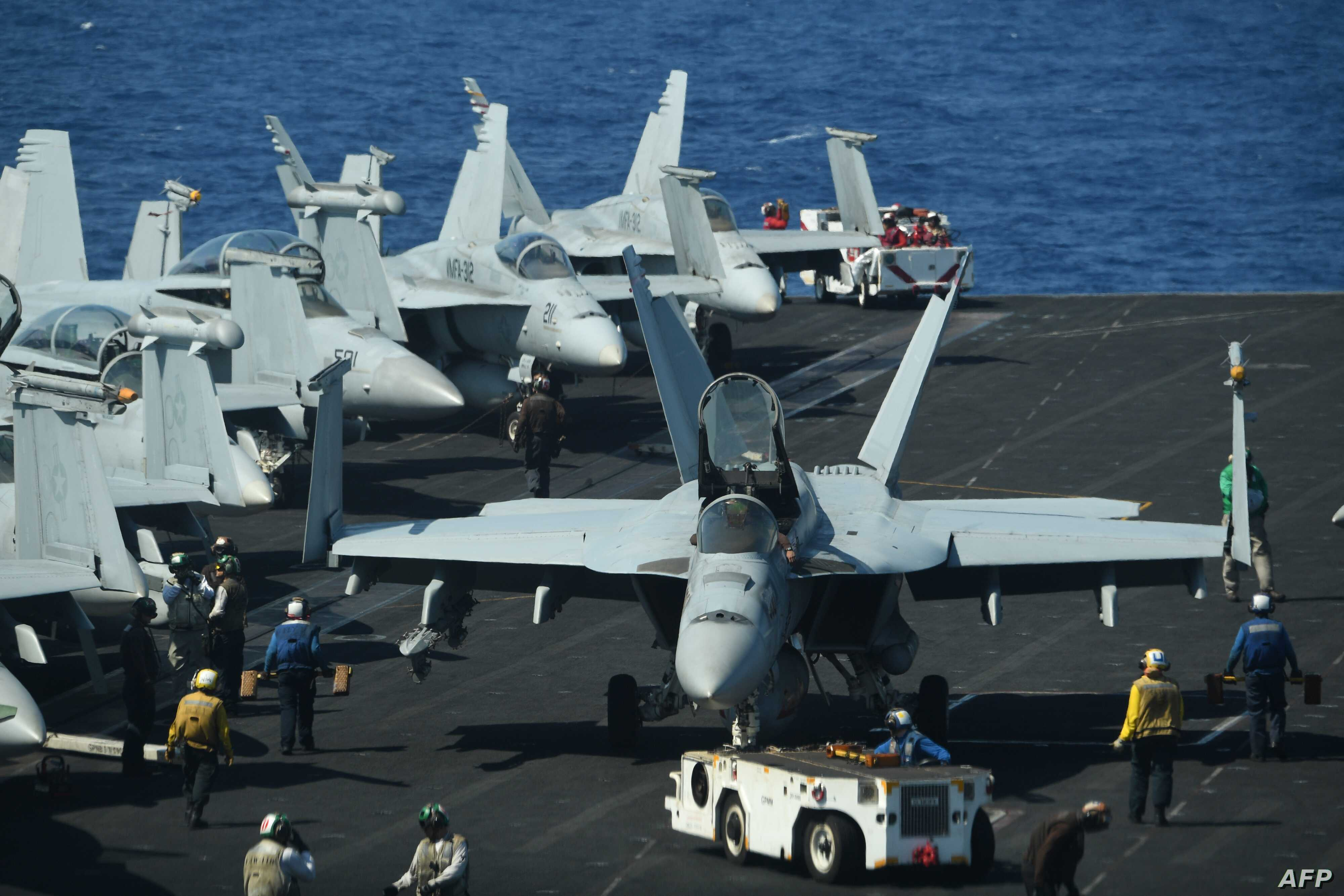 Sailors preapre FA-18 Hornet fighter jets for take off during a routine training aboard the US aircraft carrier Theodore Roosevelt in the South China sea on April 10, 2018.