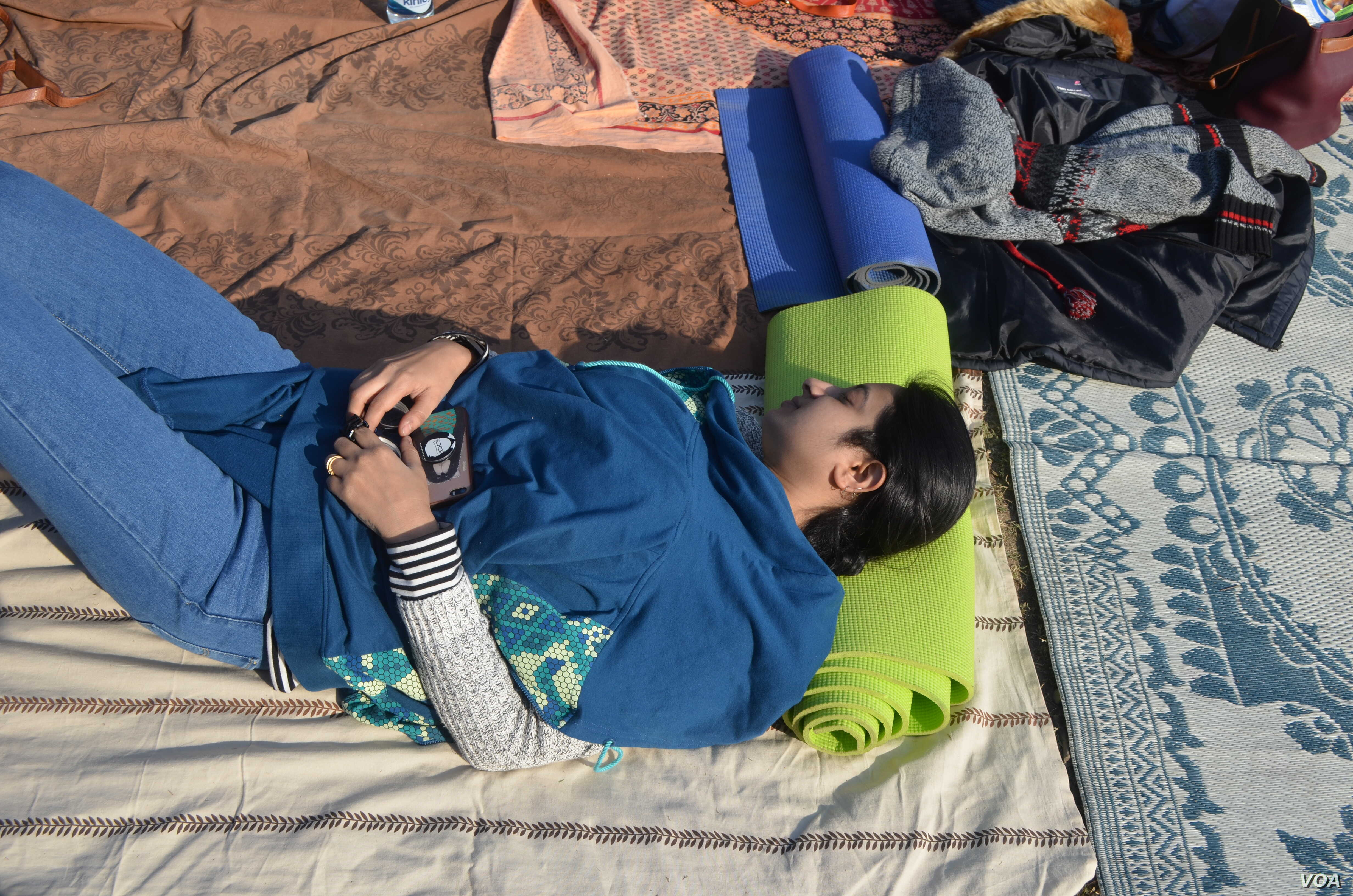 """A woman takes a symbolic nap at a park in New Delhi as part of a """"Meet to Sleep"""" campaign initiated to highlight the need for more safety for women. (A. Pasricha/VOA)"""