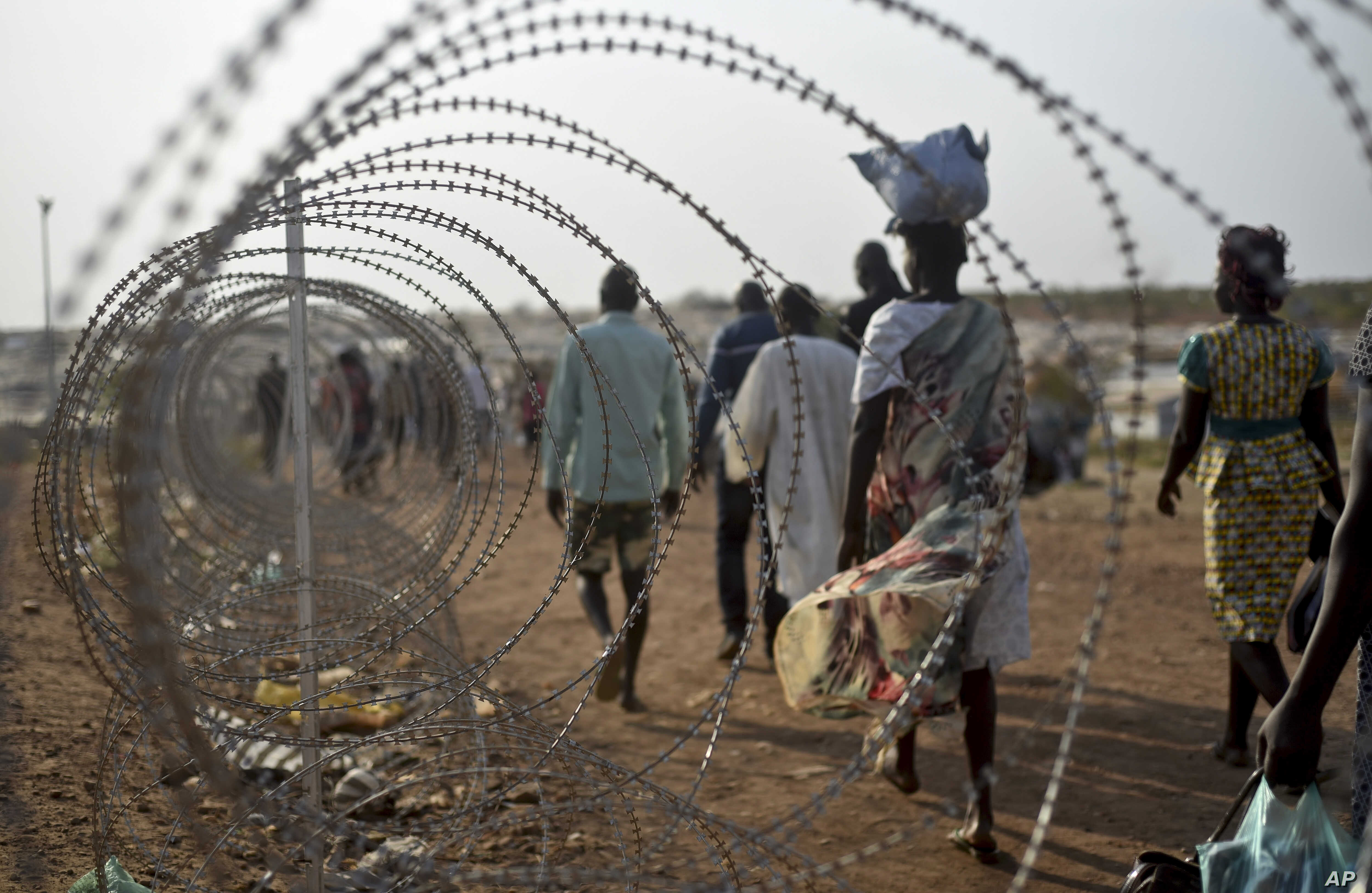 A file photo taken Jan. 19, 2016 shows displaced people walking next to a razor wire fence at the United Nations base in the capital Juba, South Sudan.