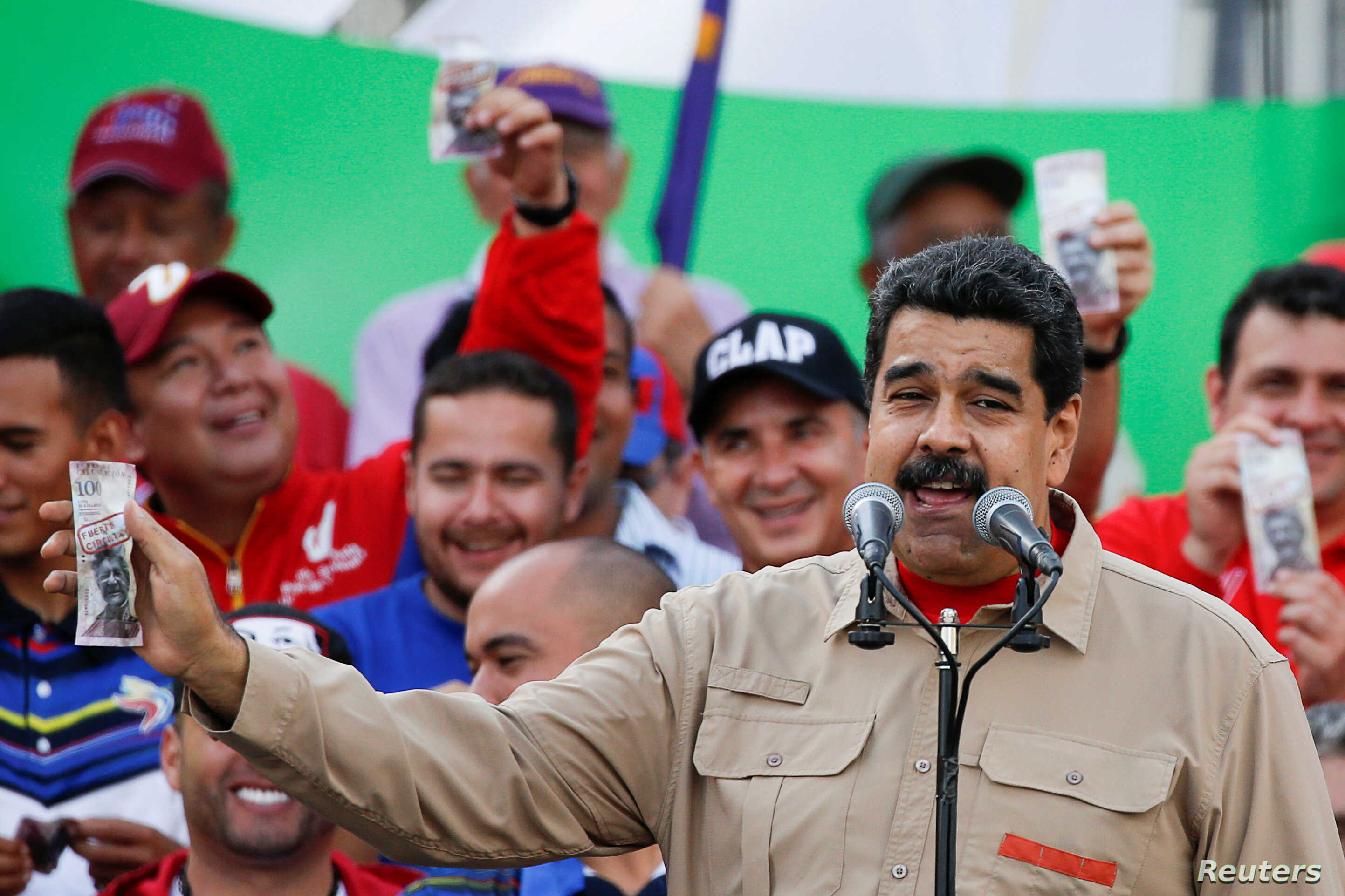 Venezuela's President Nicolas Maduro holds up a mock 100-bolivar bill depicting the president of the National Assembly Henry Ramos Allup, during a pro-government rally in Caracas, Venezuela, Dec. 17, 2016.