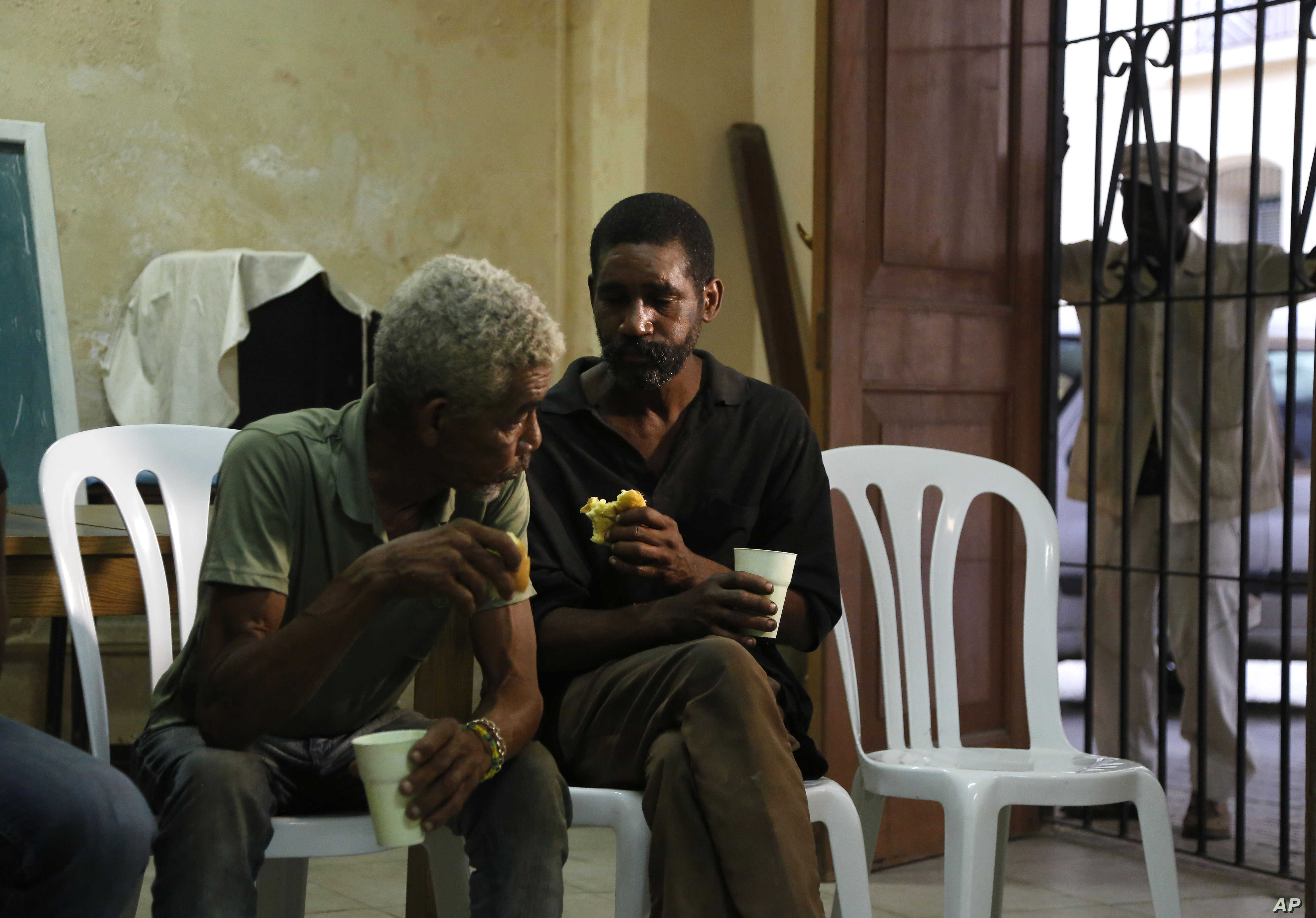In this Aug. 21, 2015, photo, men helped by the San Egidio Church eat snacks in its community center in Havana, Cuba.