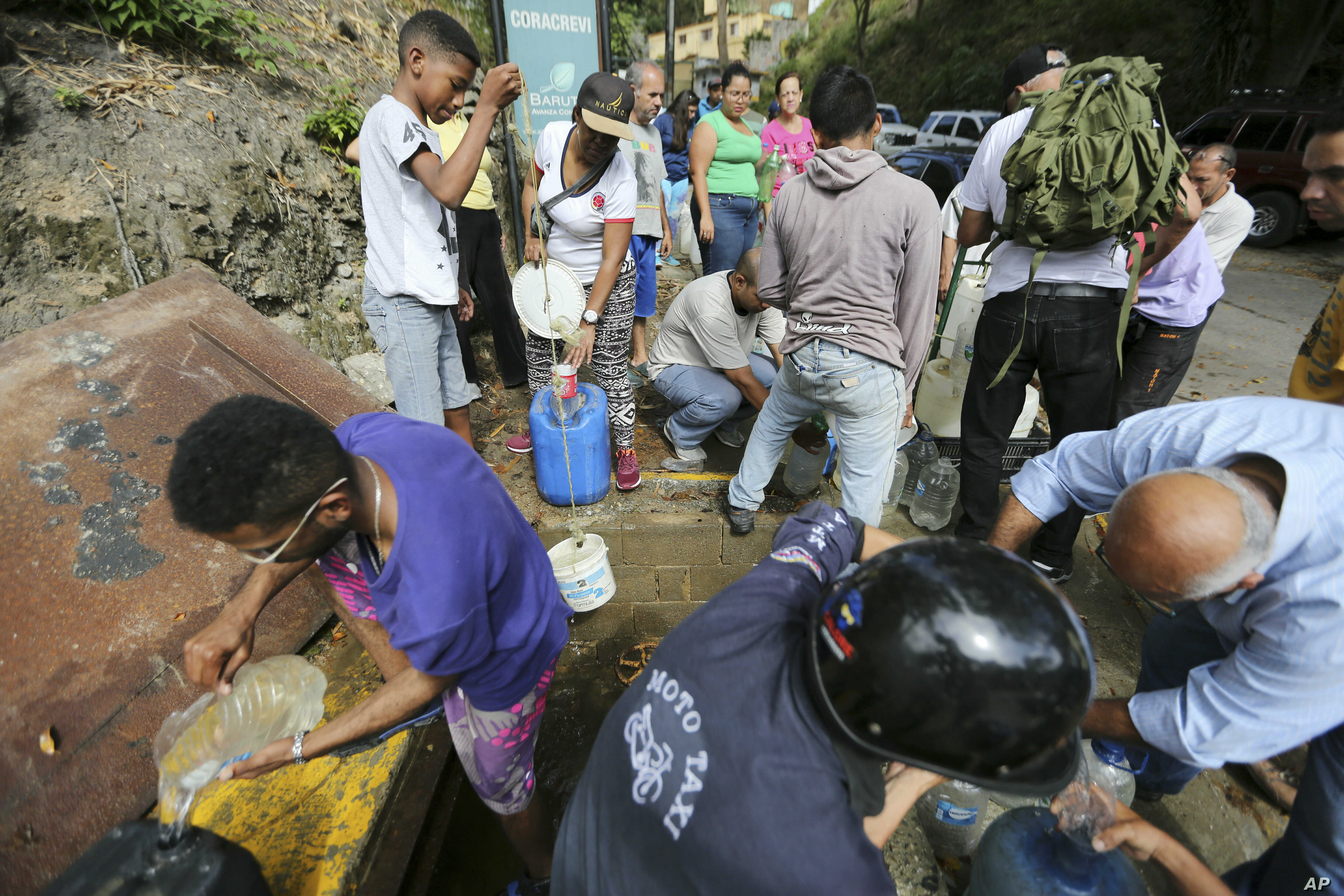People collect water from an open pipeline during rolling blackouts, which affects the water pumps in people's homes and apartment buildings, in Caracas, Venezuela, Monday, March 11, 2019.