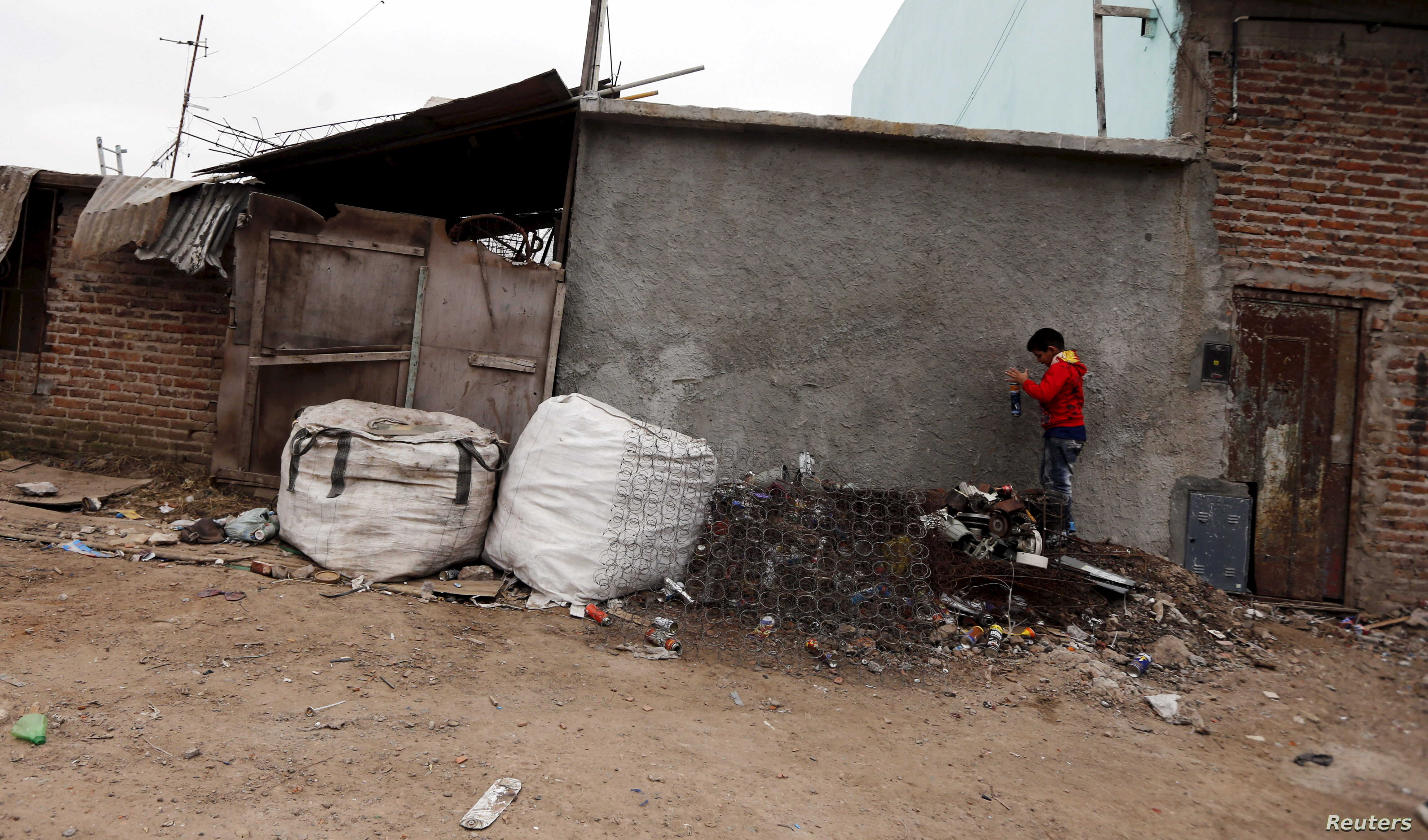 A boy plays with cans over a pile of garbage outside his home in the Villa Palito slum in La Matanza, in the greater Buenos Aires area, July 29, 2015.