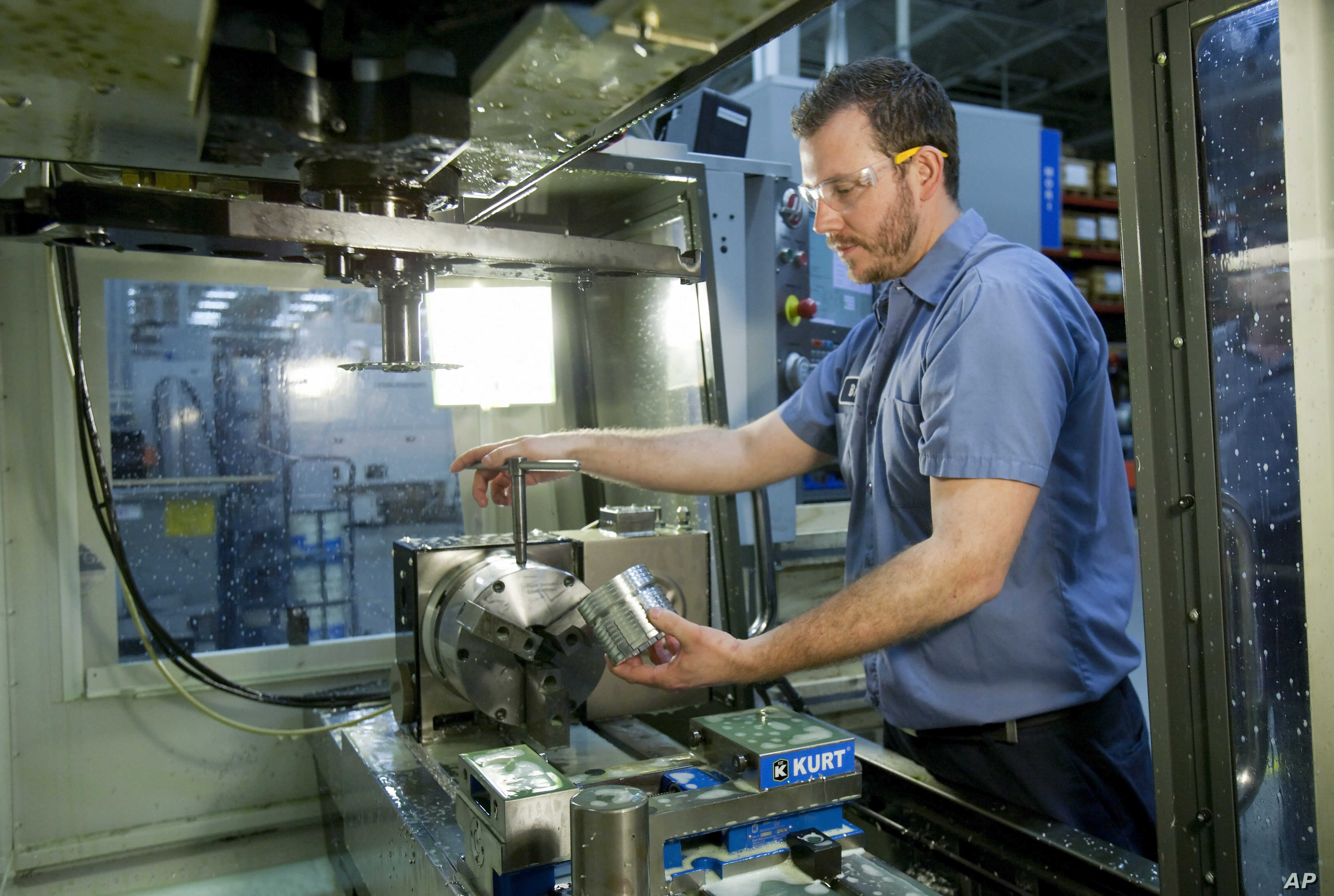 FILE — Brian Gasiewski, who received training at Macomb Community College, removes an external housing for an industrial shock absorber from a CNC  machine at Fitzpatrick Manufacturing Co. in Sterling Heights, Michigan.