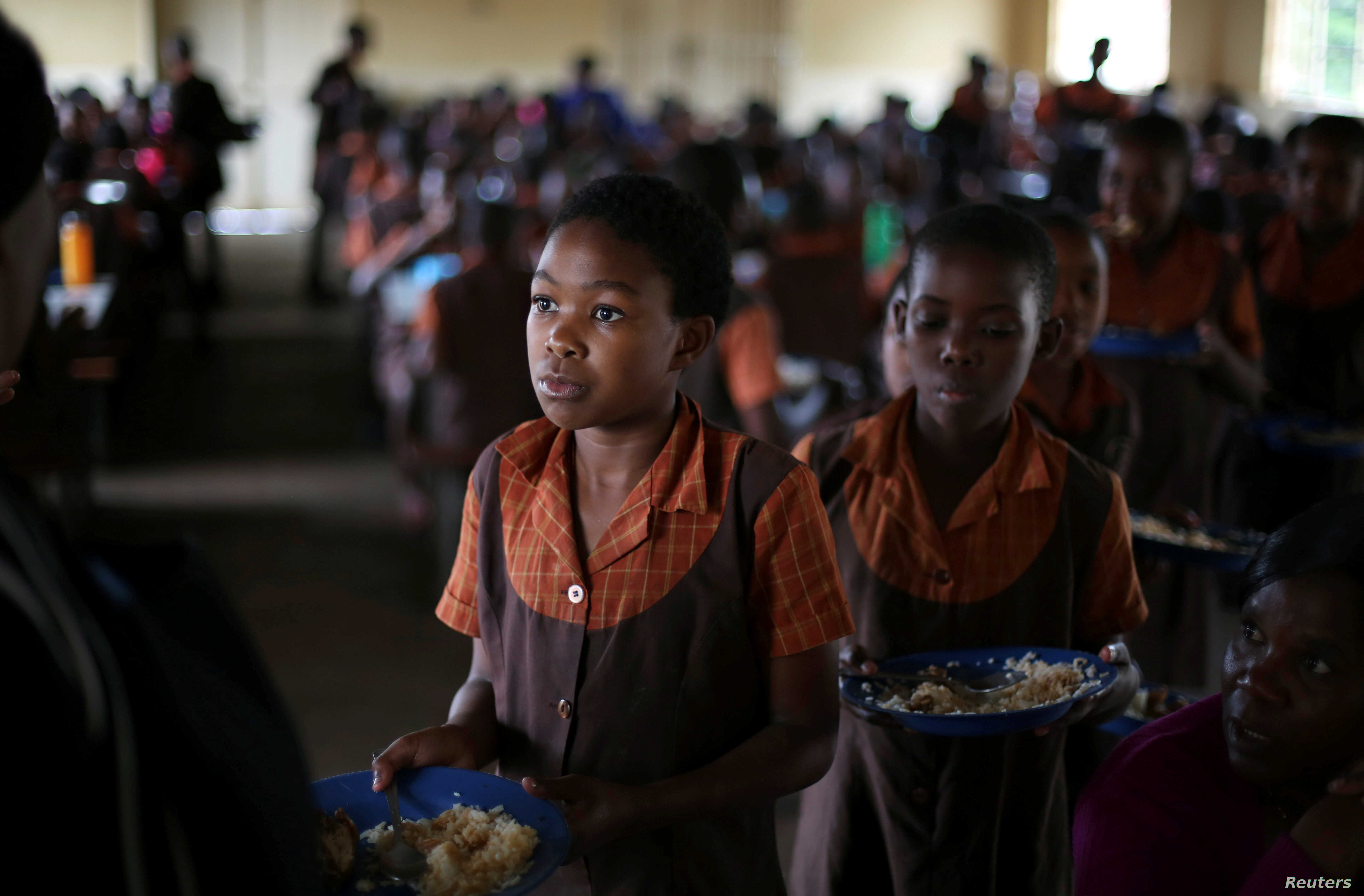 FILE - School children are served lunch at a primary school near Harare, Zimbabwe, Nov. 26, 2017.