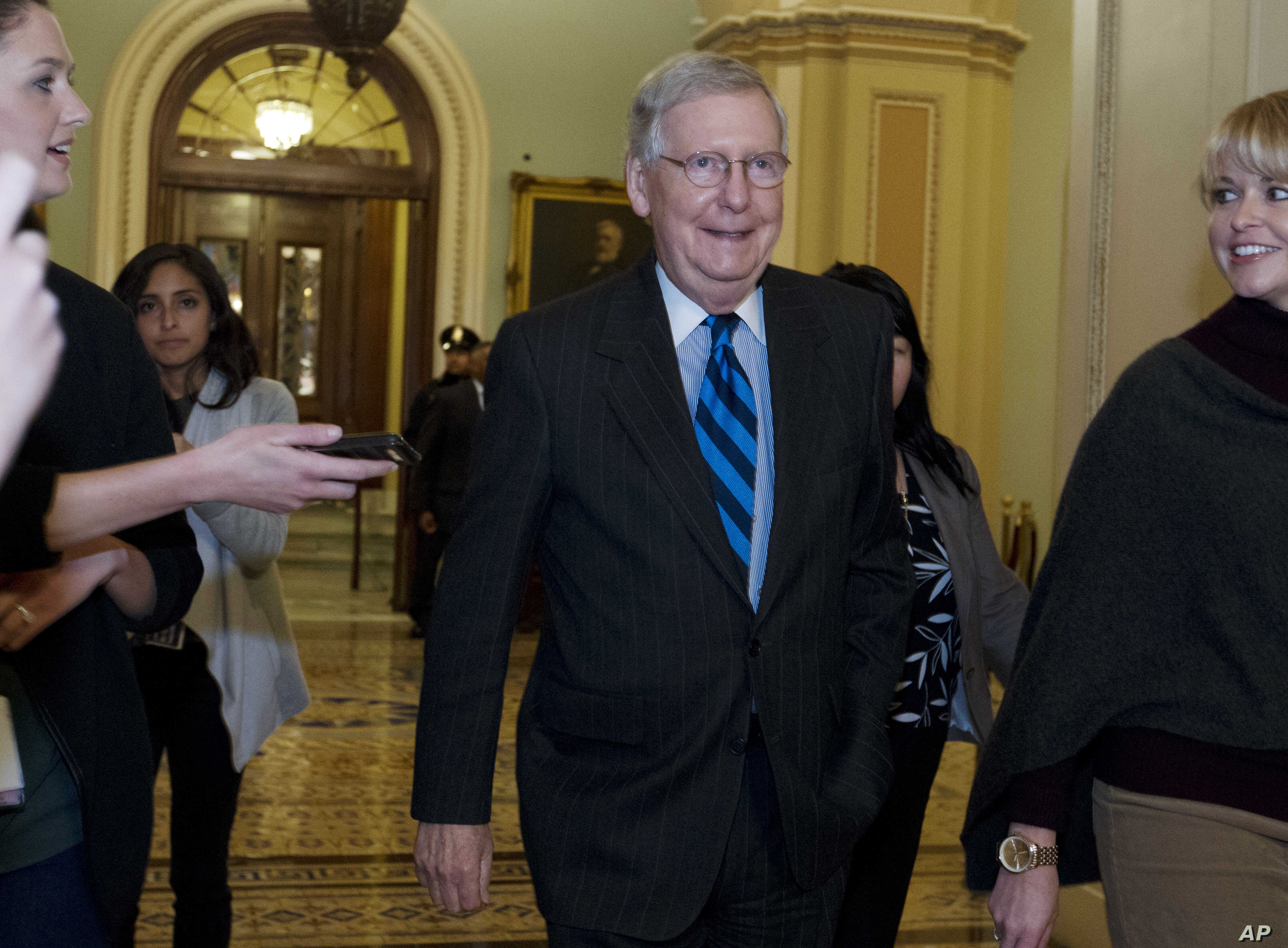 Senate Majority Leader Mitch McConnell, R-Ky., listens to questions from reporters as he walks to his office after speaking on the Senate floor at the Capitol, Sunday, Jan. 21, 2018, in Washington.