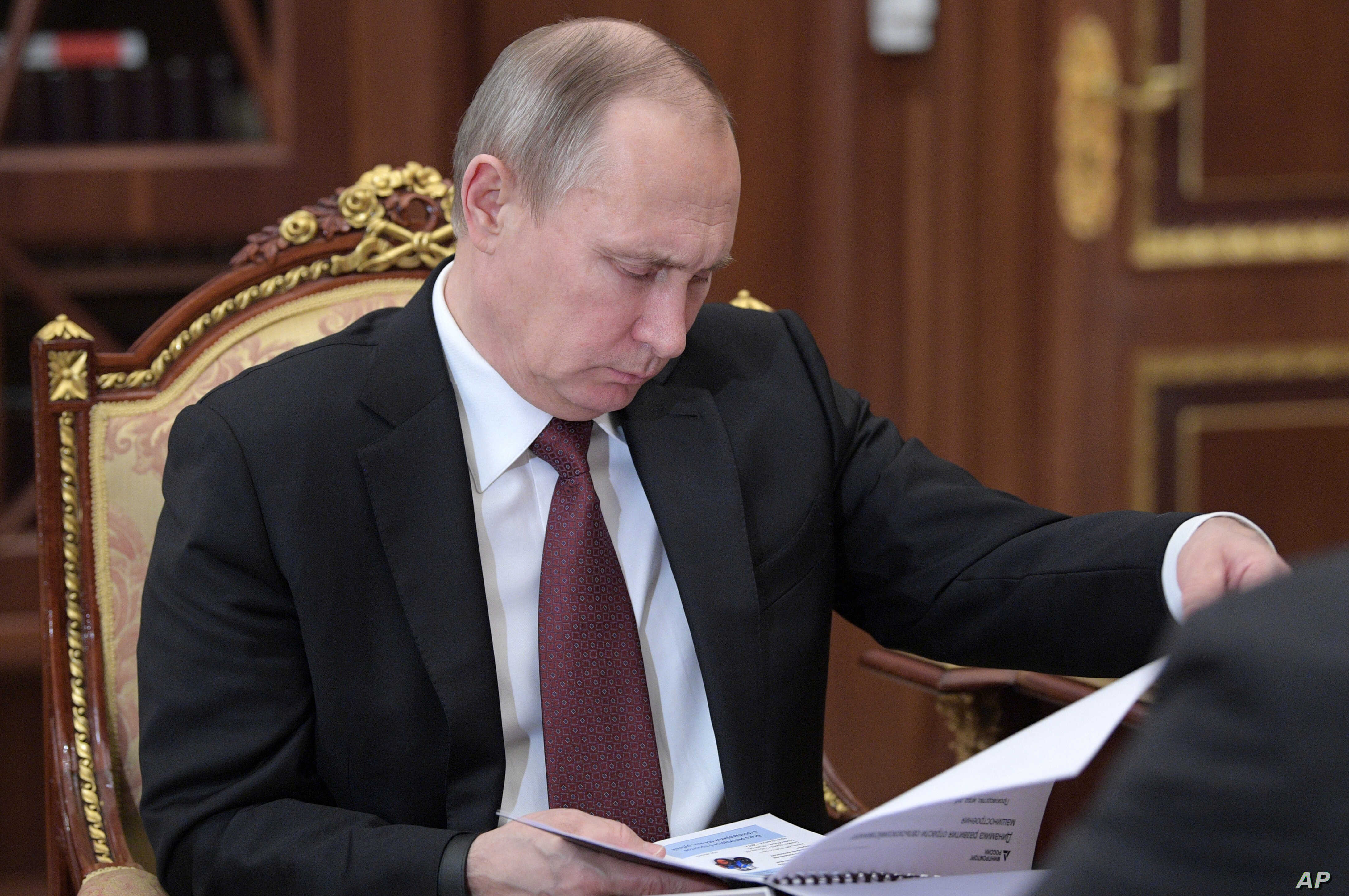 Russian President Vladimir Putin reads papers during a meeting in the Kremlin, in Moscow, Russia, Jan. 16, 2017.