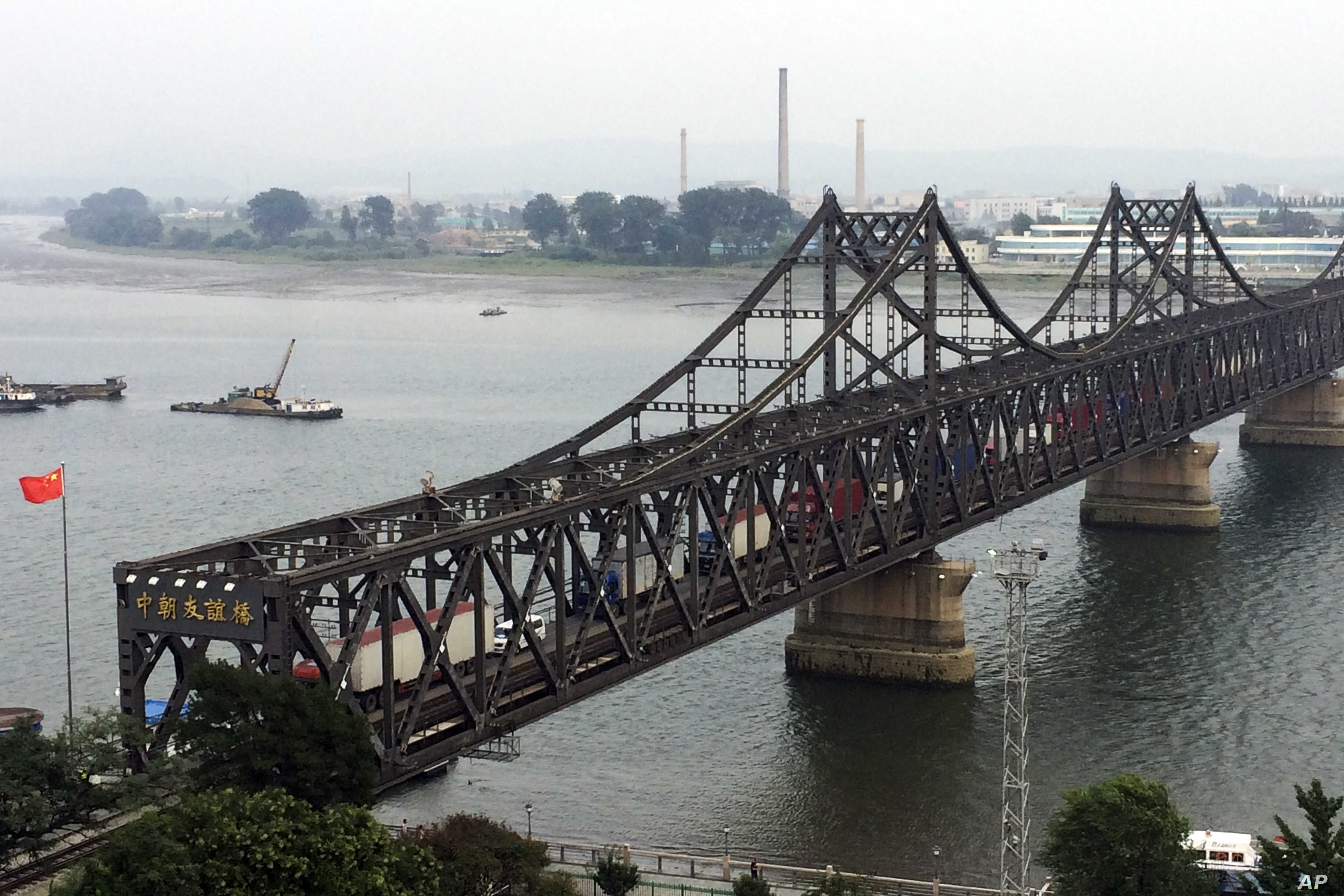 FILE - Trucks cross the friendship bridge connecting China and North Korea in the Chinese border town of Dandong, opposite side of the North Korean town of Sinuiju, Sept. 4, 2017. For Chinese traders, United Nations sanctions on North Korea are a dis...