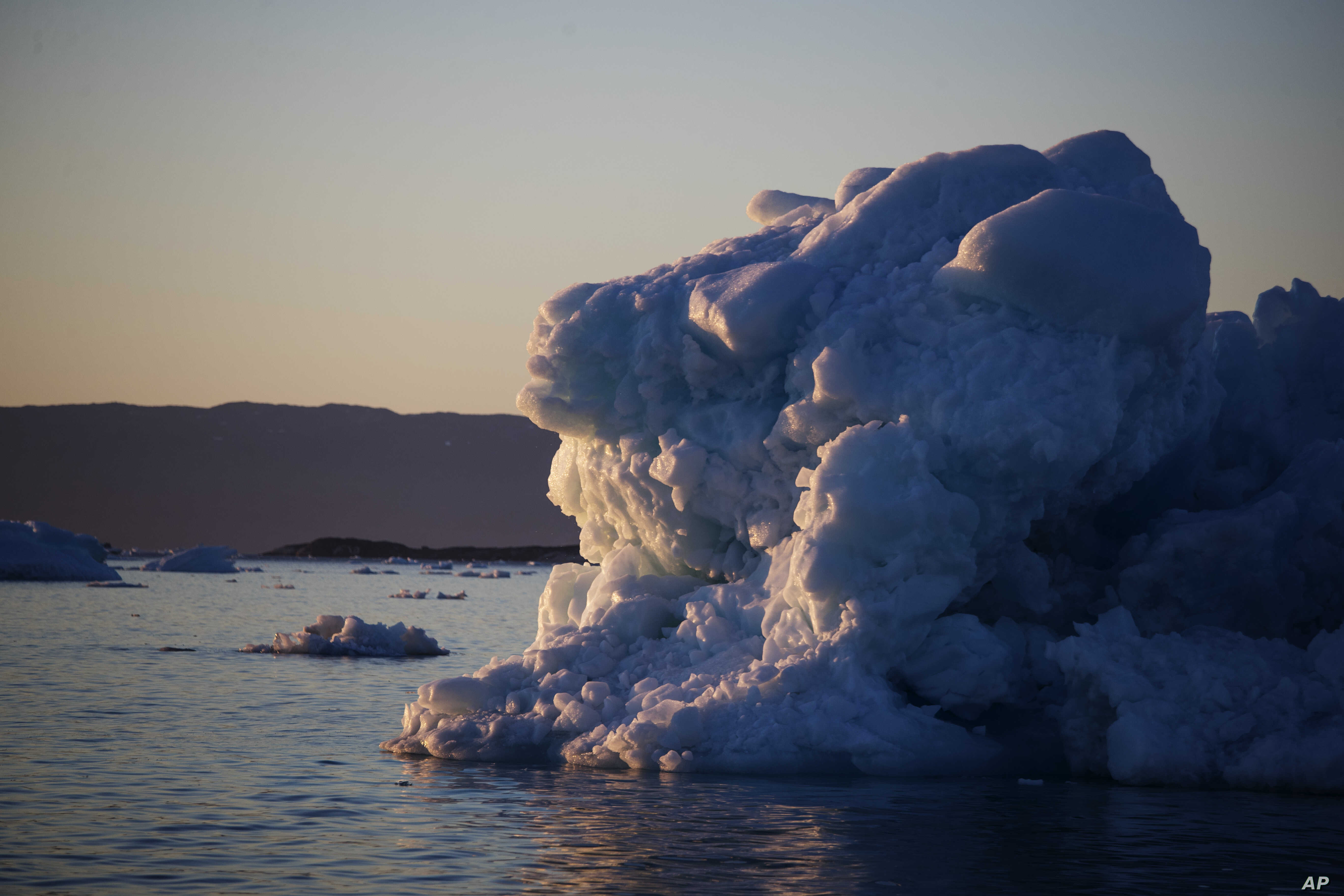 The suns sets against an iceberg floating in the Nuup Kangerlua Fjord near Nuuk in southwestern Greenland, Aug. 1, 2017. Greenland's glaciers have been melting and retreating at an accelerated pace in recent years due to warmer temperatures.