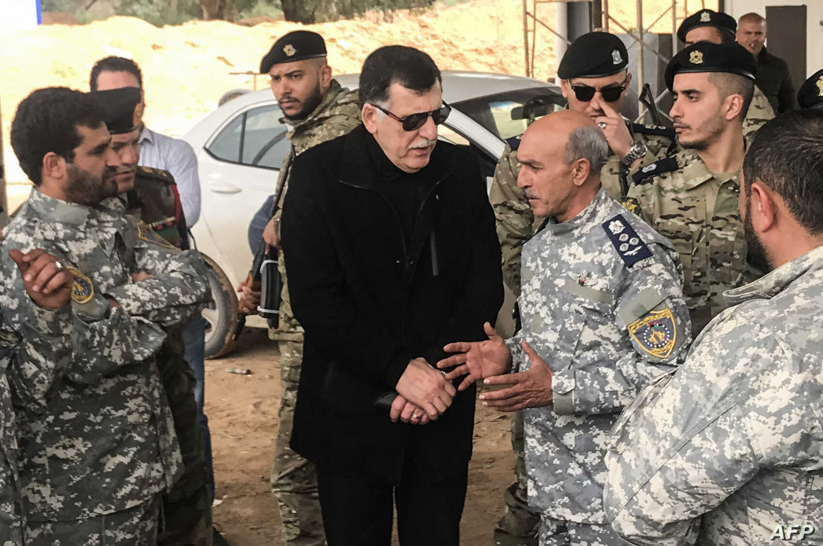 The head of Libya's UN-backed unity government, Fayez al-Sarraj, center, visits military and security commanders of the government forces who supervised recapture of the checkpoint 27 in Janzour, between Tripoli and the coastal town of Zawiya, April ...