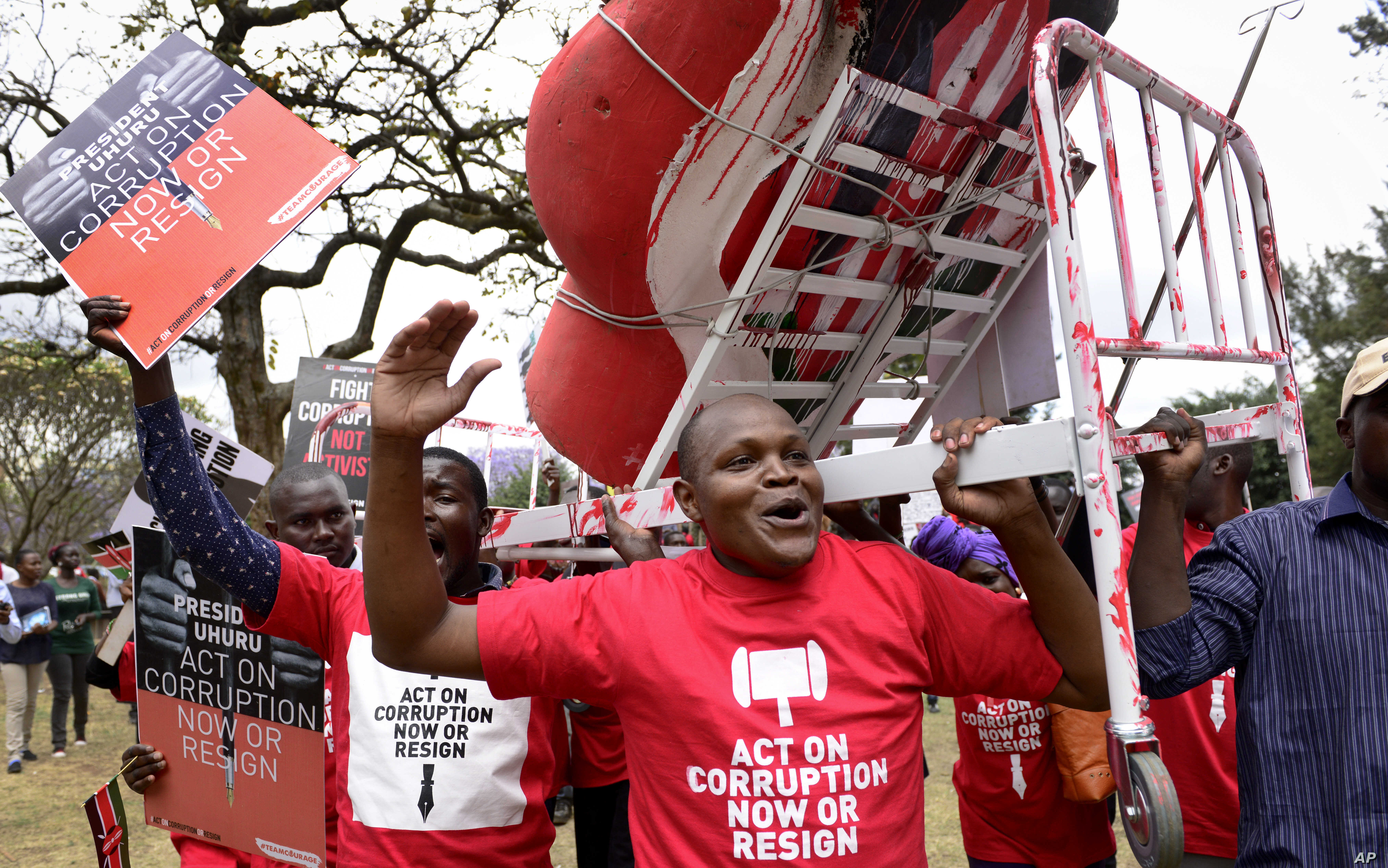 Kenya Corruption: Demonstrators carry a mock hospital bed covered in fake blood to illustrate the slogan that Kenyans are bleeding due to poor hospital services caused by corruption, in Nairobi, Kenya Thursday, Nov. 3, 2016.