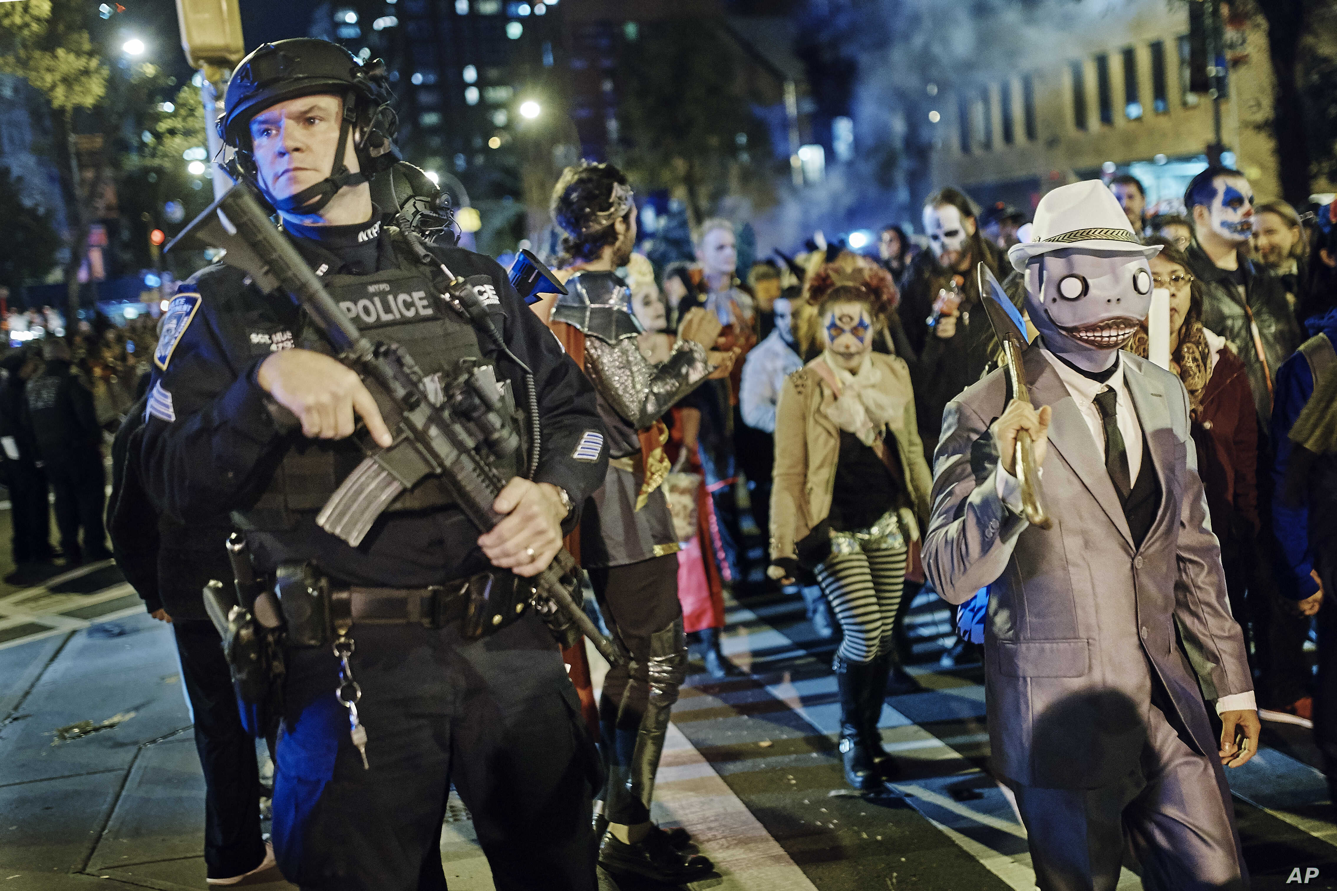 Heavily armed police guard as revelers march during the Greenwich Village Halloween Parade in New York, Oct. 31, 2017.