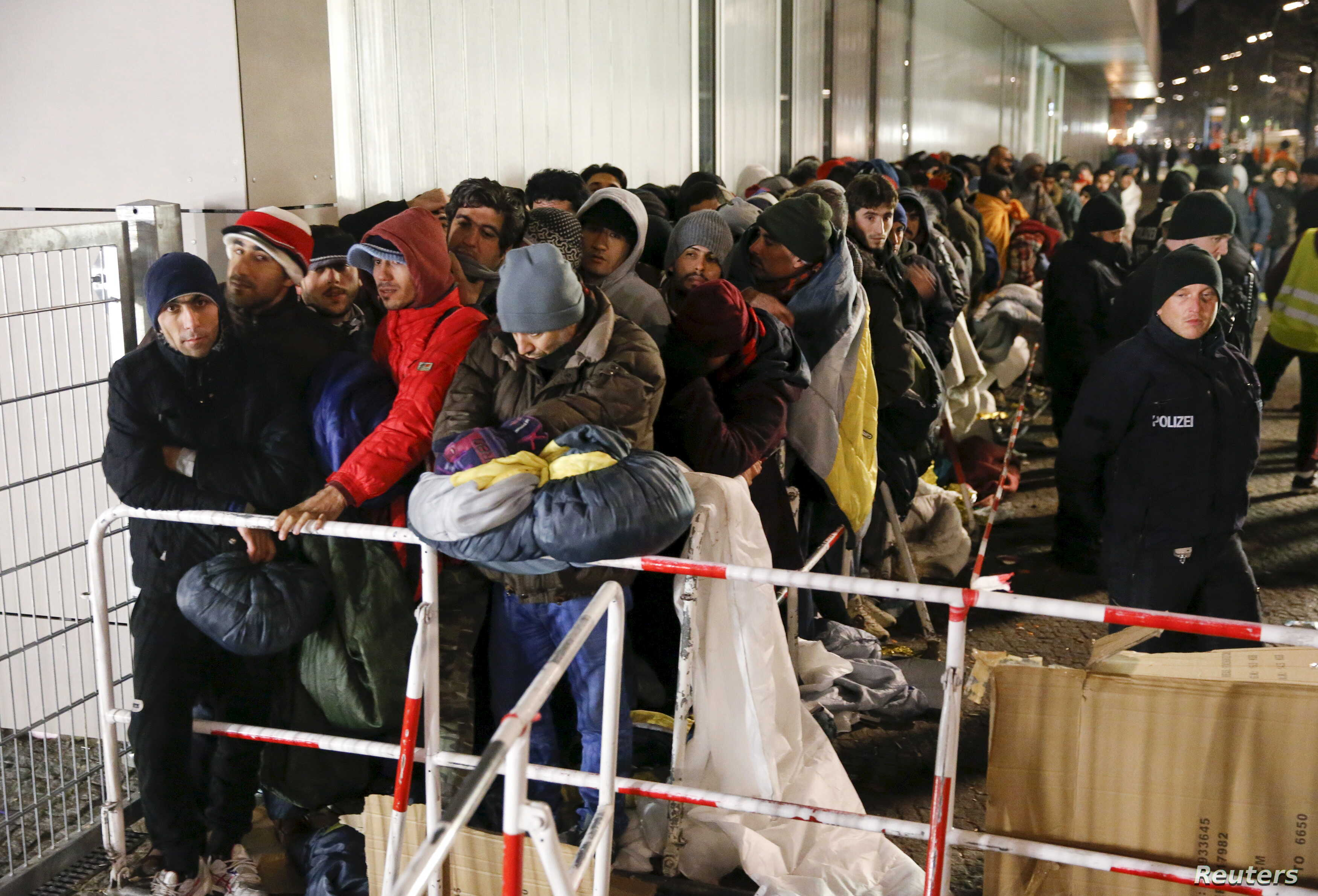Migrants queue on a street to enter the compound outside the Berlin Office of Health and Social Affairs (LAGESO) for their registration process in Berlin, Germany, Dec. 9, 2015.