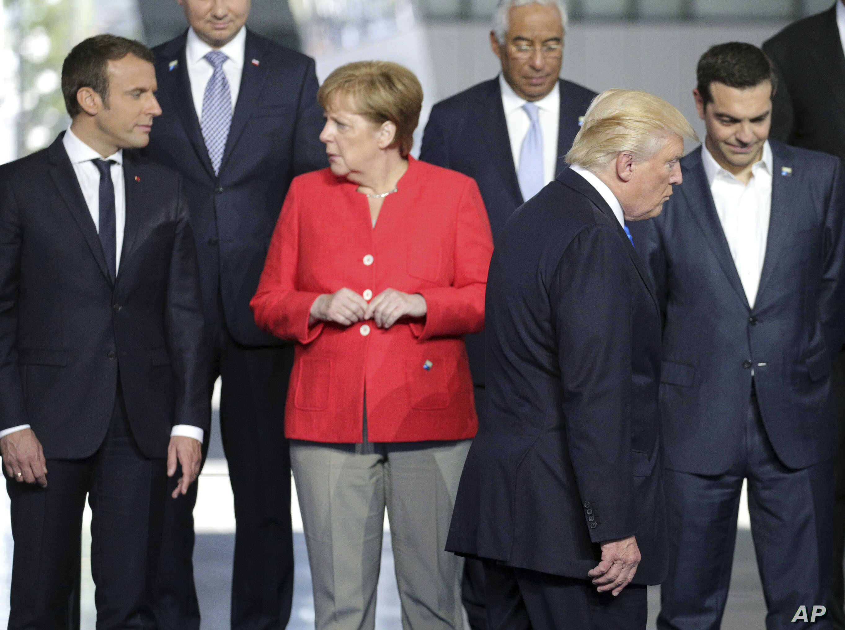 file - French President Emmanuel Macron, left, speaks with German Chancellor Angela Merkel, second left, as U.S. President Donald Trump walks to take his position during a group photo at the new NATO headquarters in Brussels on Thursday, May 25, 2017