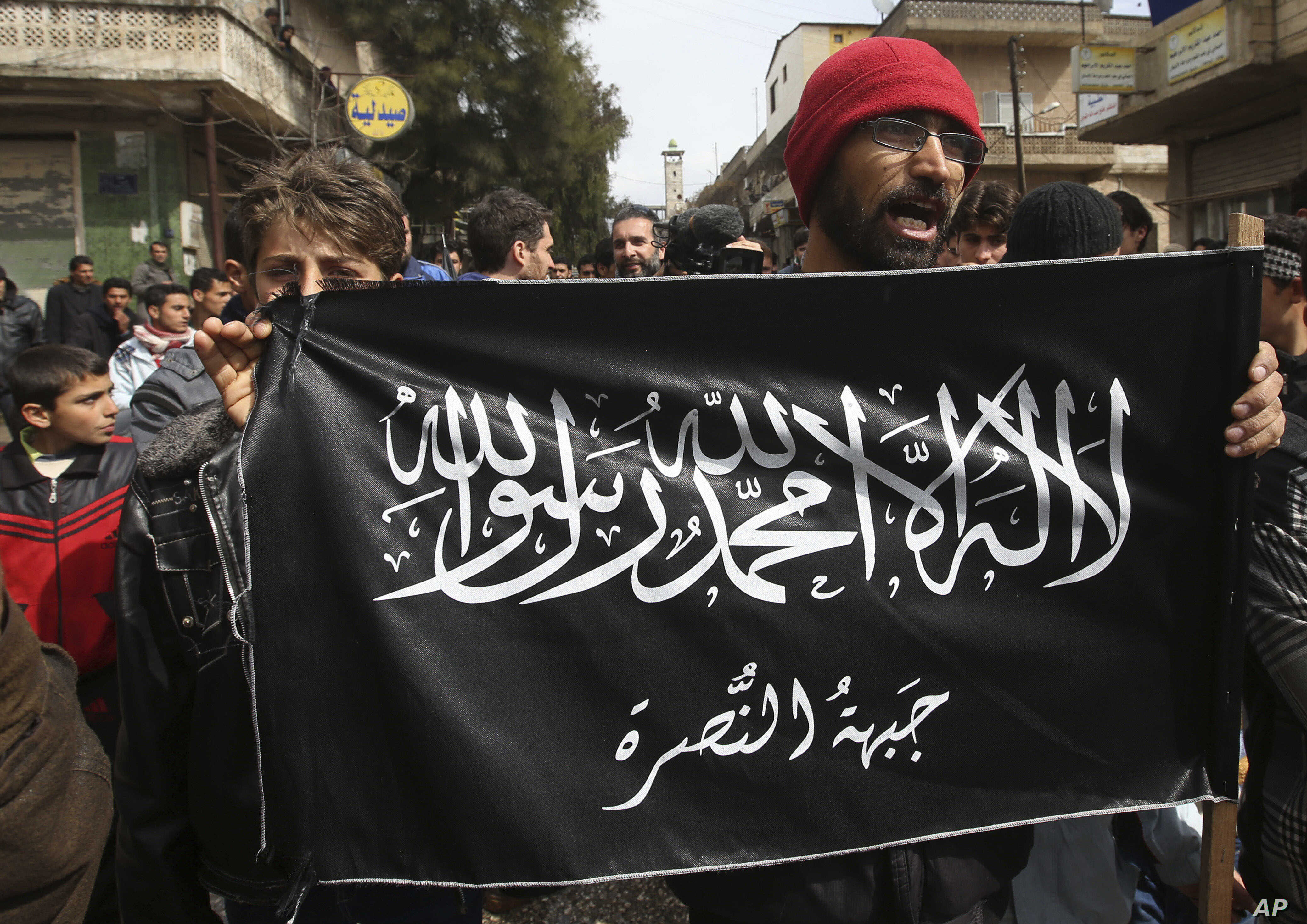 FILE - Anti-Syrian President Bashar Assad protesters hold the Jabhat al-Nusra flag, as they shout slogans during a demonstration, in Kafranbel, Idlib province, northern Syria, March 1, 2013.