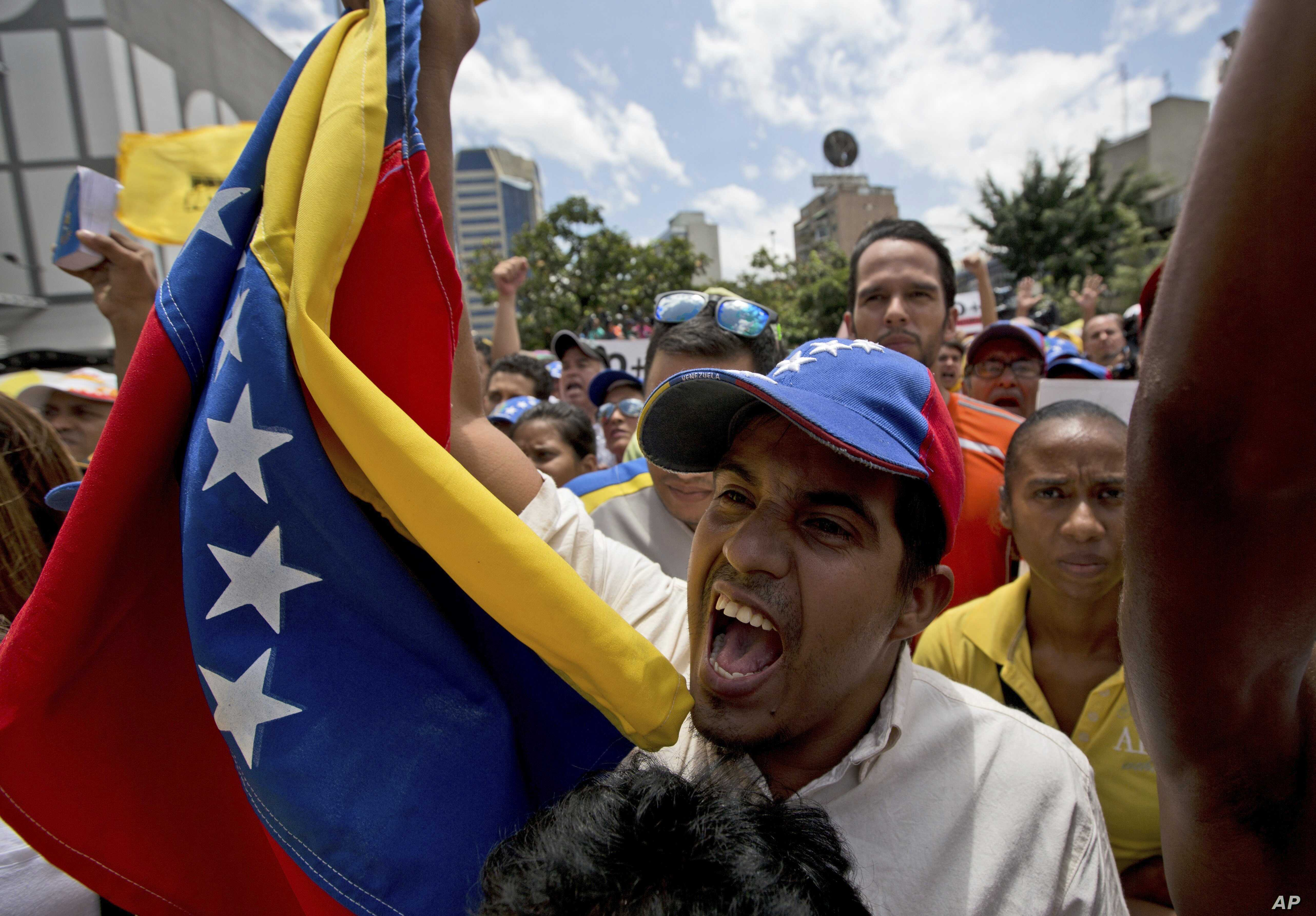 An opposition member waves a Venezuelan flag as National Assembly President Julio Borges speaks during a special public session at a square in Caracas, Venezuela, April 1, 2017.
