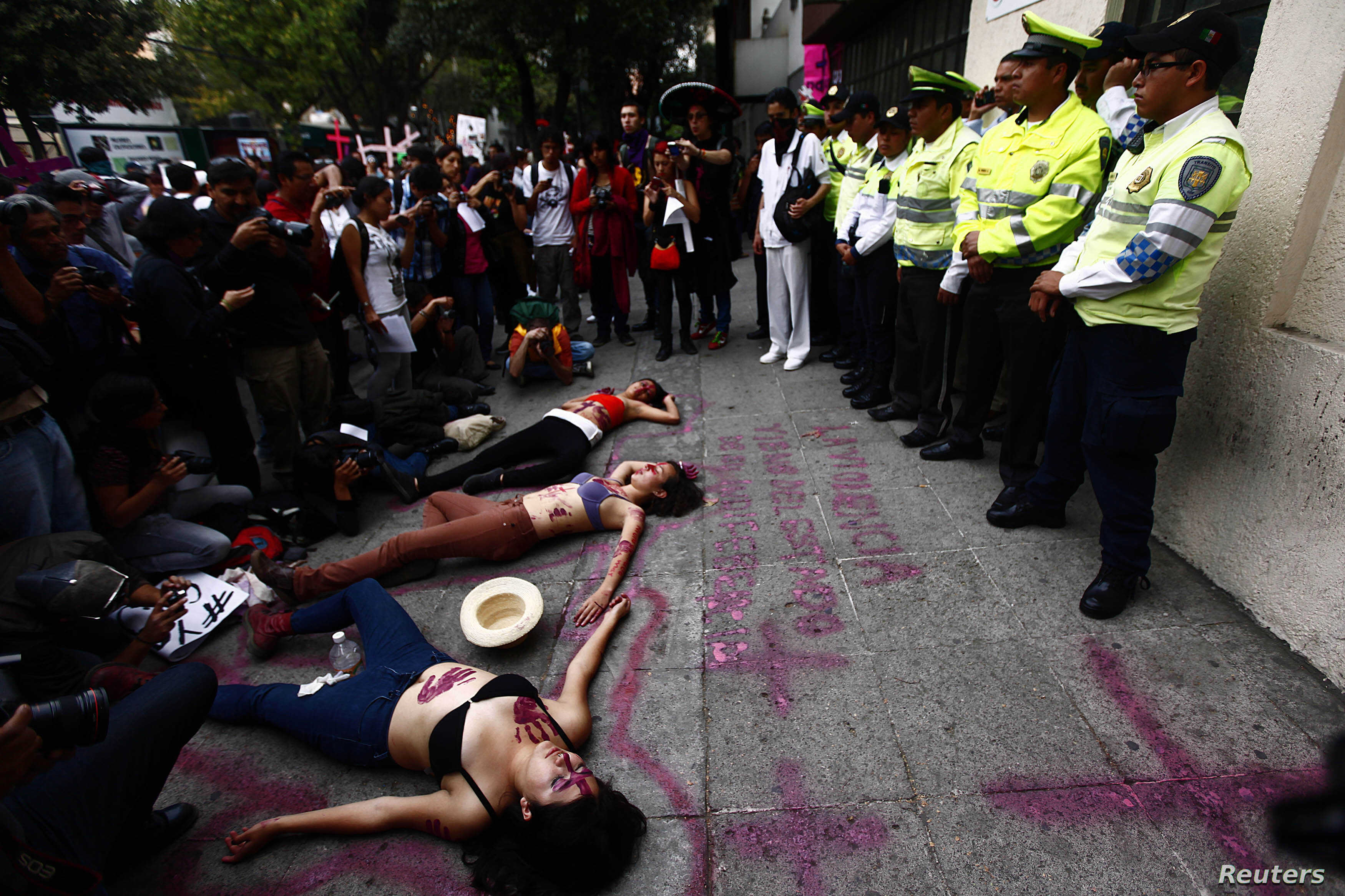 Women lie on the ground during a performance in front of traffic police officers on the sidelines of a demonstration to demand justice for women who are the victims of violence, in Mexico City March 8, 2013. Activists and relatives of women who were ...