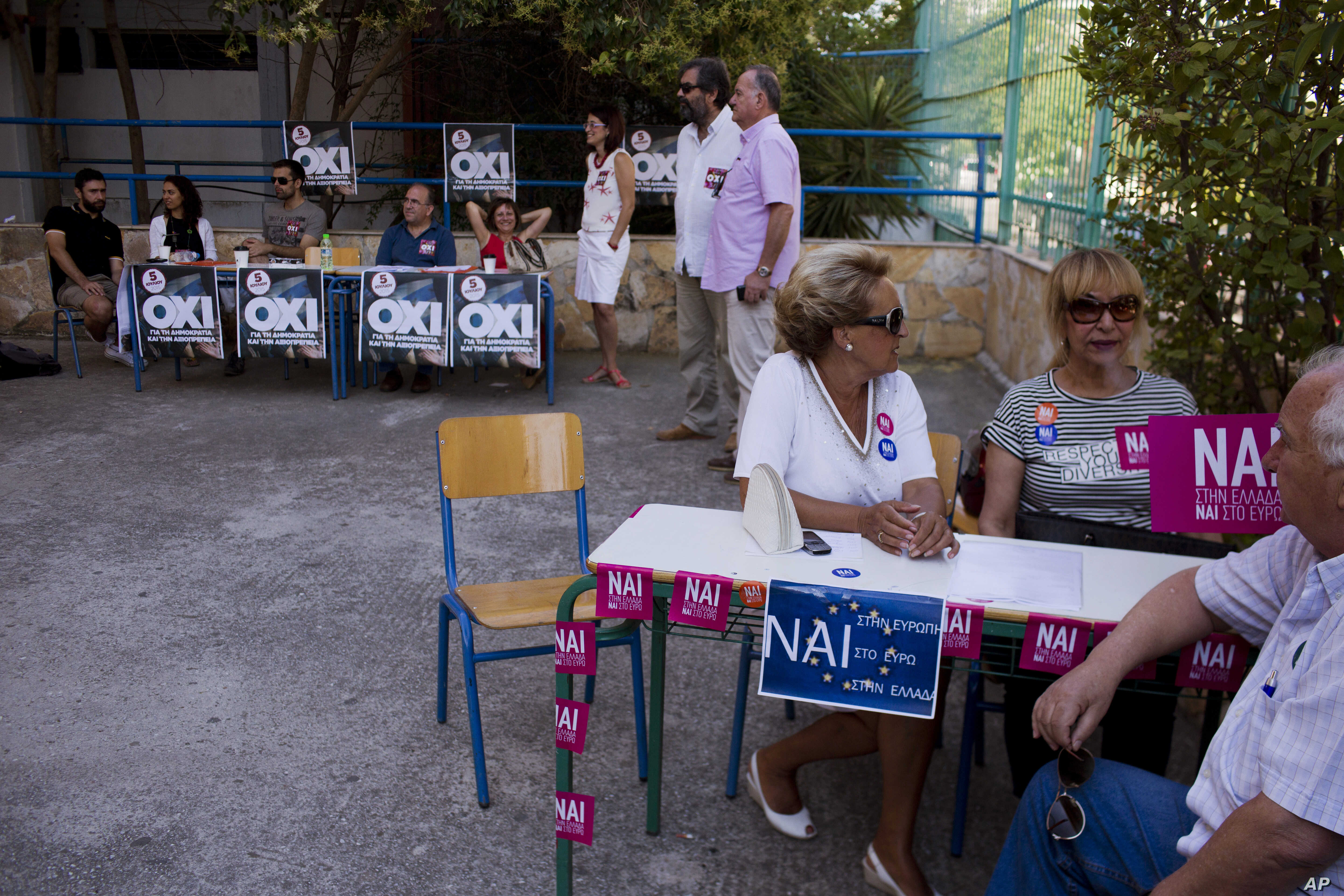 """Supporters of """"yes,"""" right, and of """"no,"""" left, wait for voters arriving in a polling station in Athens, July 5, 2015."""