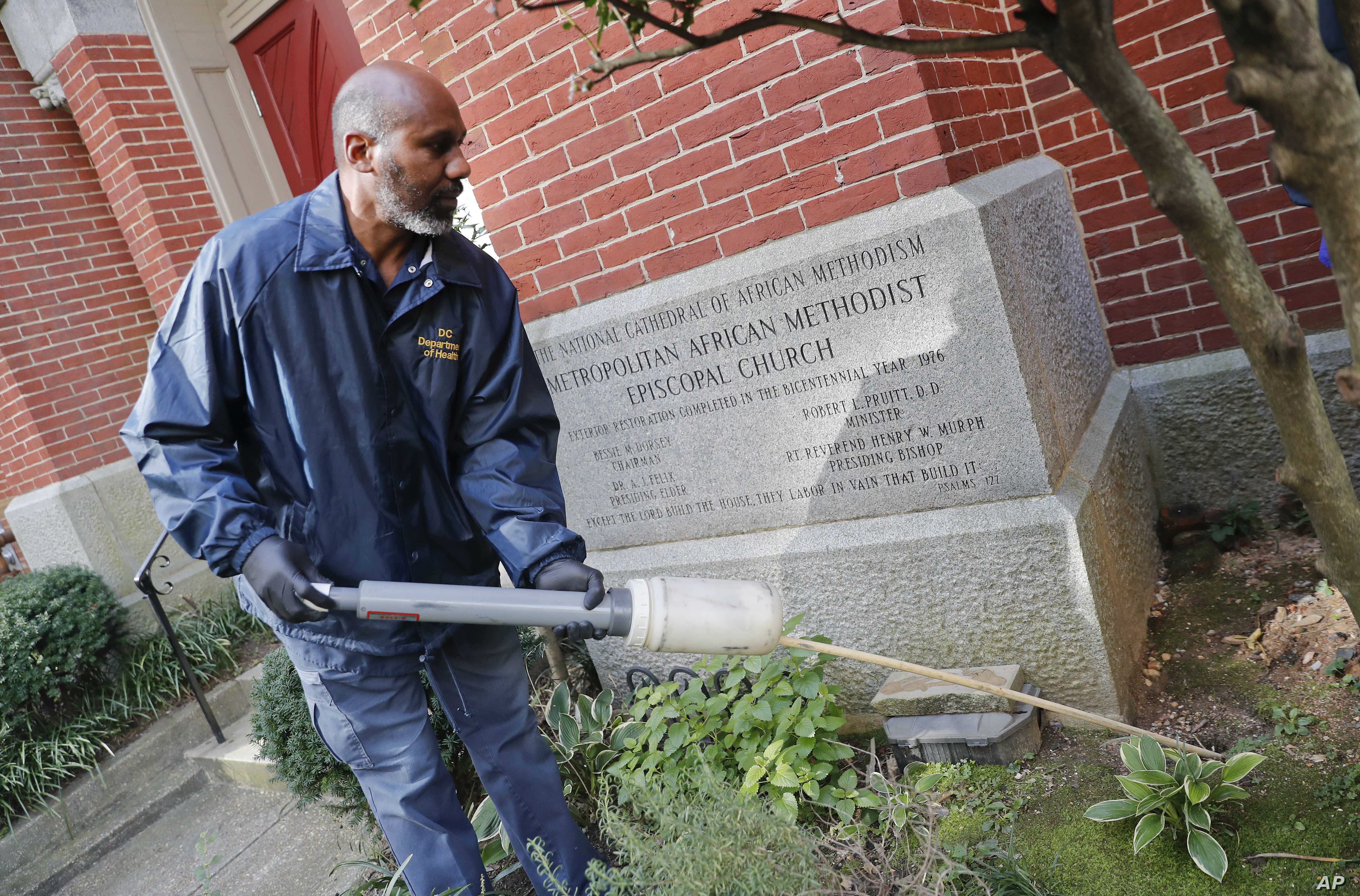 Pest Control Officer Gregory Cornes, from the D.C. Department of Health's Rodent Control Division, uses a duster to pump poison into rat burrows, found on the grounds of Metropolitan African Methodist Episcopal Church in downtown Washington, Oct. 17,...