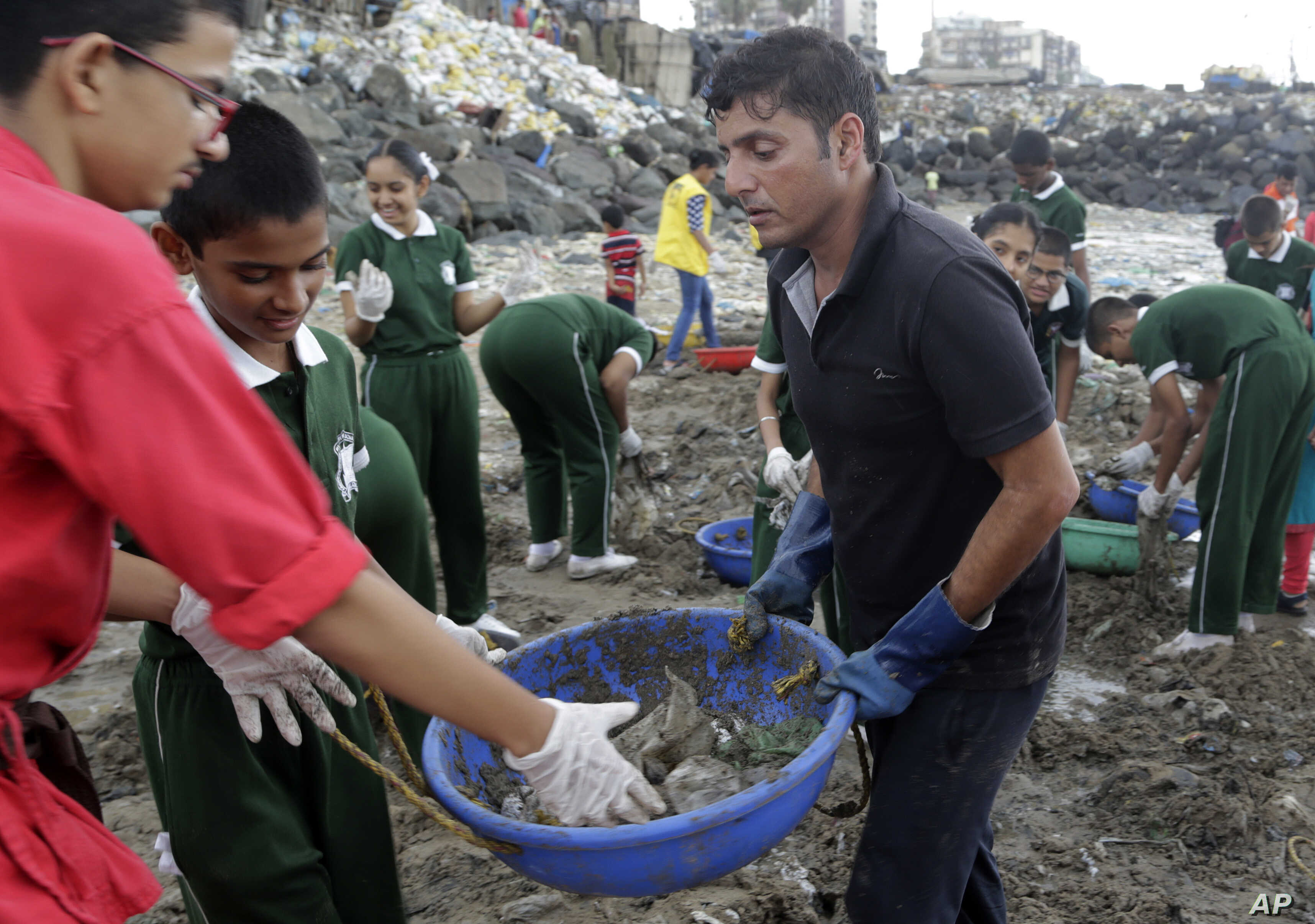 Afroz Shah, in black, participates in a clean up drive with school children at the Versova beach on the Arabian Sea coast in Mumbai, India.