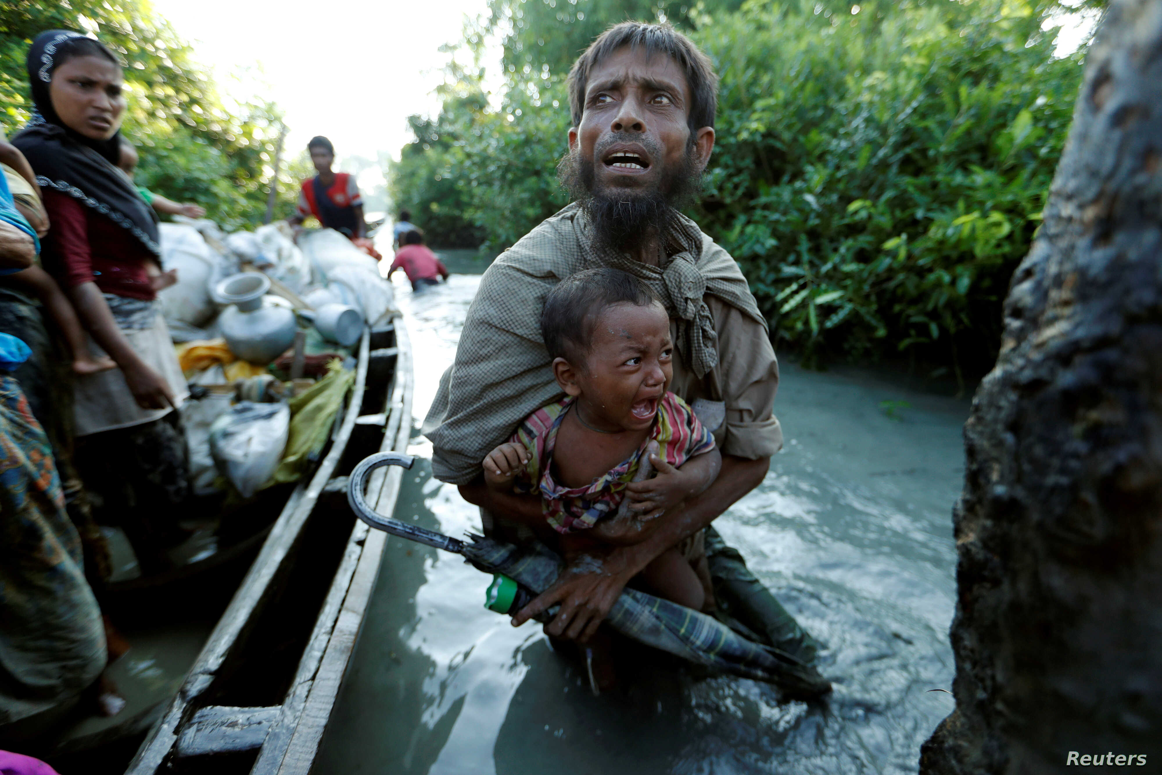 FILE - Rohingya refugees arrive to the Bangladeshi side of the Naf River after crossing the border from Myanmar, in Palang Khali, Bangladesh, Oct. 16, 2017.