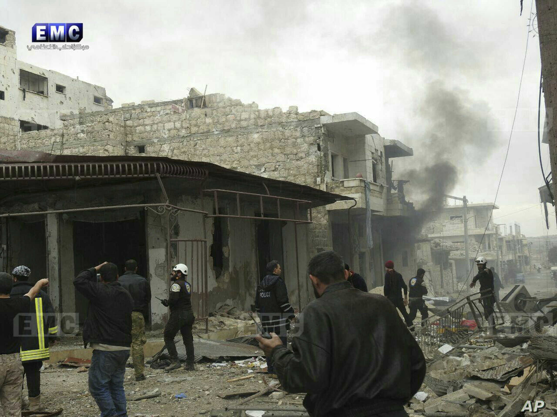 FILE - This photo provided by the Syrian anti-government activist group EMC shows members of the Syrian civil defense known as the White Helmets, gathering at a street which was attacked by Russian airstrikes, in Maarat al-Nuaman town, southern Idlib...