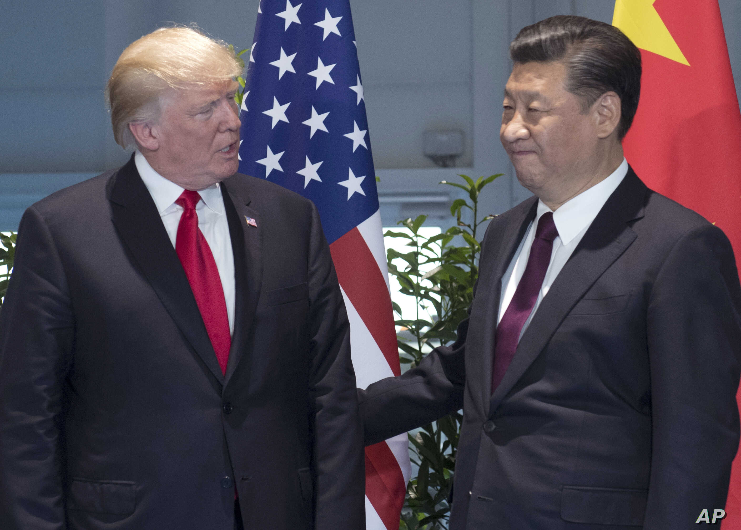 FILE - , U.S. President Donald Trump, left, and Chinese President Xi Jinping arrive for a meeting on the sidelines of the G-20 Summit in Hamburg, Germany.