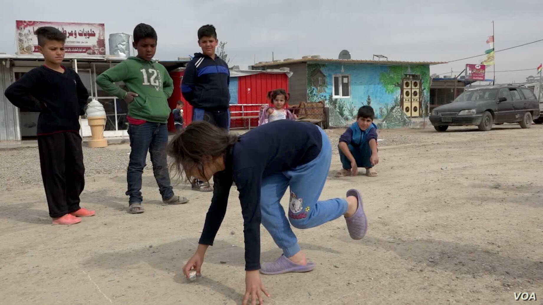 Children play in the dirt road of a Domiz, Iraq, refugee camp (VOA).