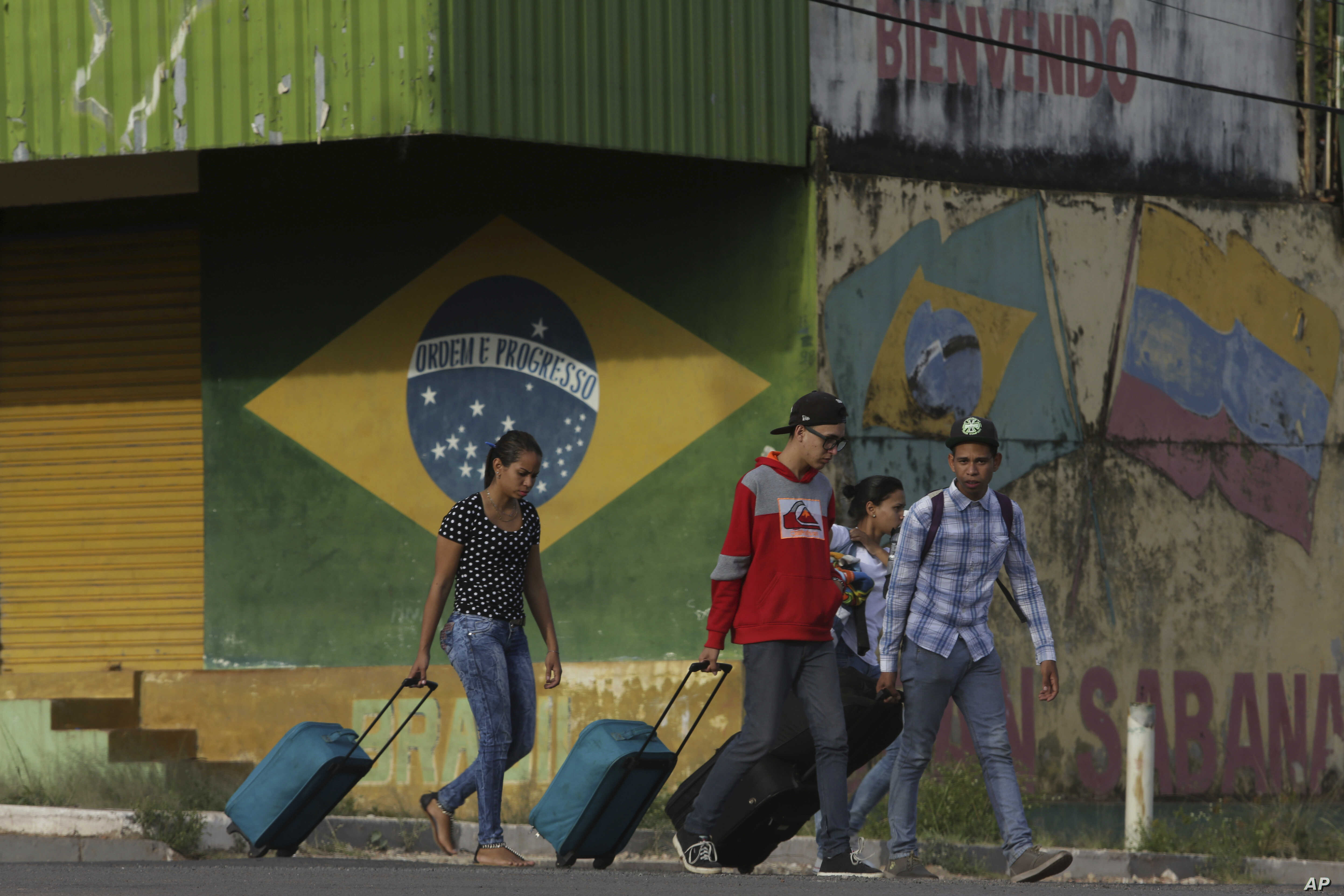 In this March 9, 2018 photo, young Venezuelans pull their luggage after crossing the border to Pacaraima, Roraima state, Brazil.