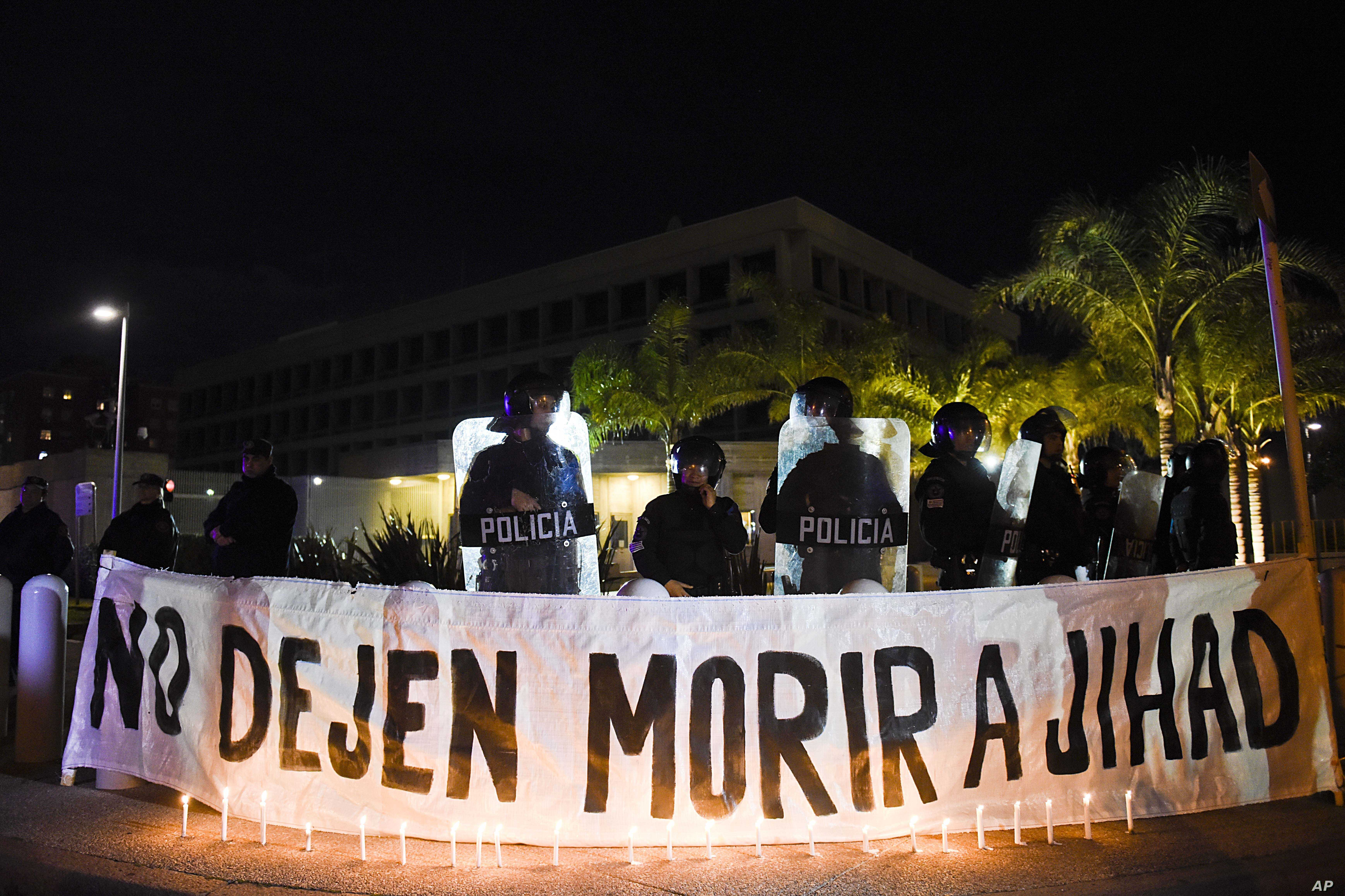 """FILE - A sign that reads in Spanish """"Don't let Jihad die"""" hangs behind candles outside the U.S. embassy during a demonstration in Montevideo, Uruguay, Sept. 16, 2016. Former Guantanamo detainee Abu Wa'el Dhiab from Syria, also called Jihad, was on a ..."""