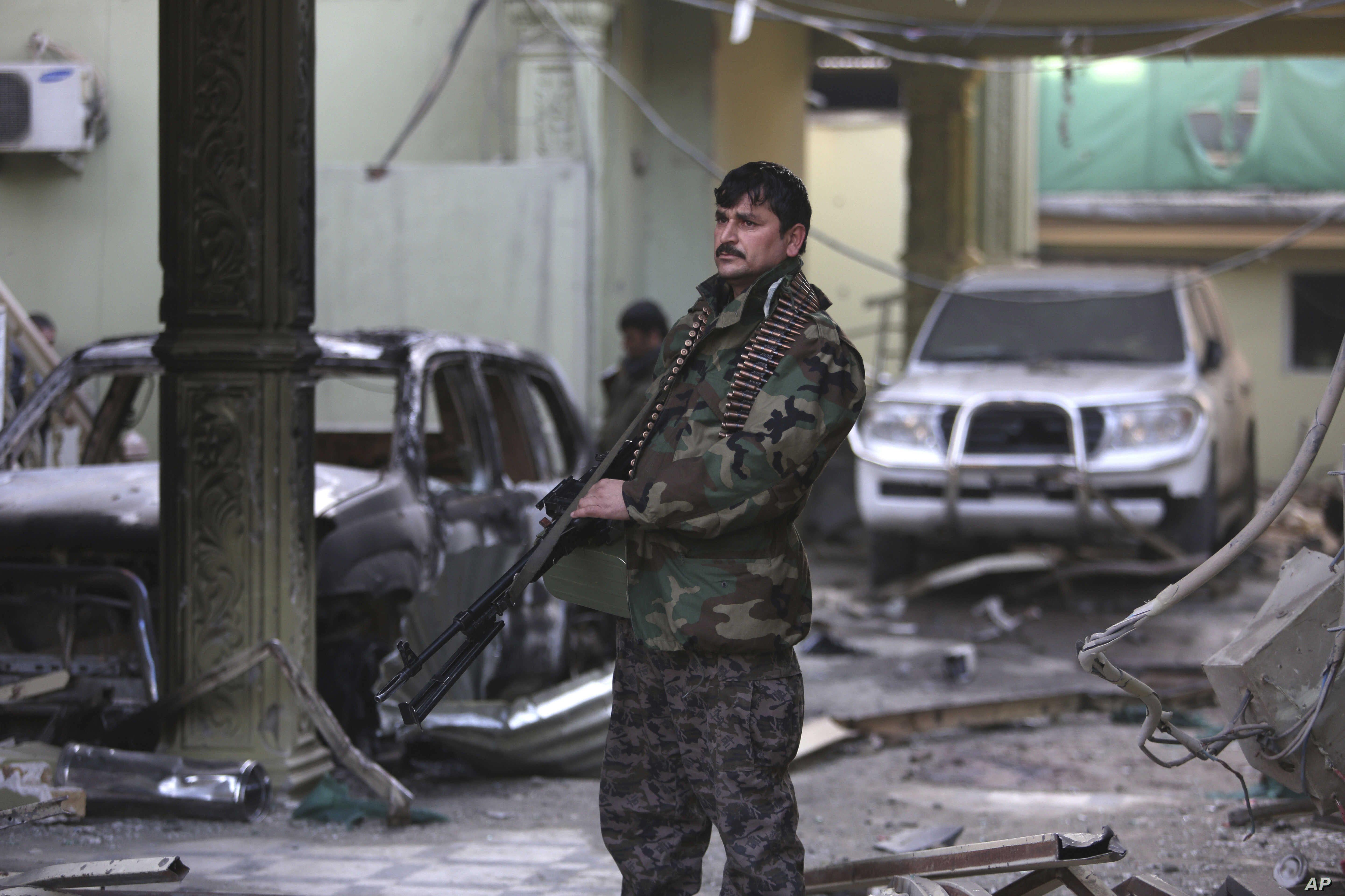 An Afghan security forces member stands guard at the Spanish Embassy after an attack in Kabul, Afghanistan, Dec. 12, 2015.