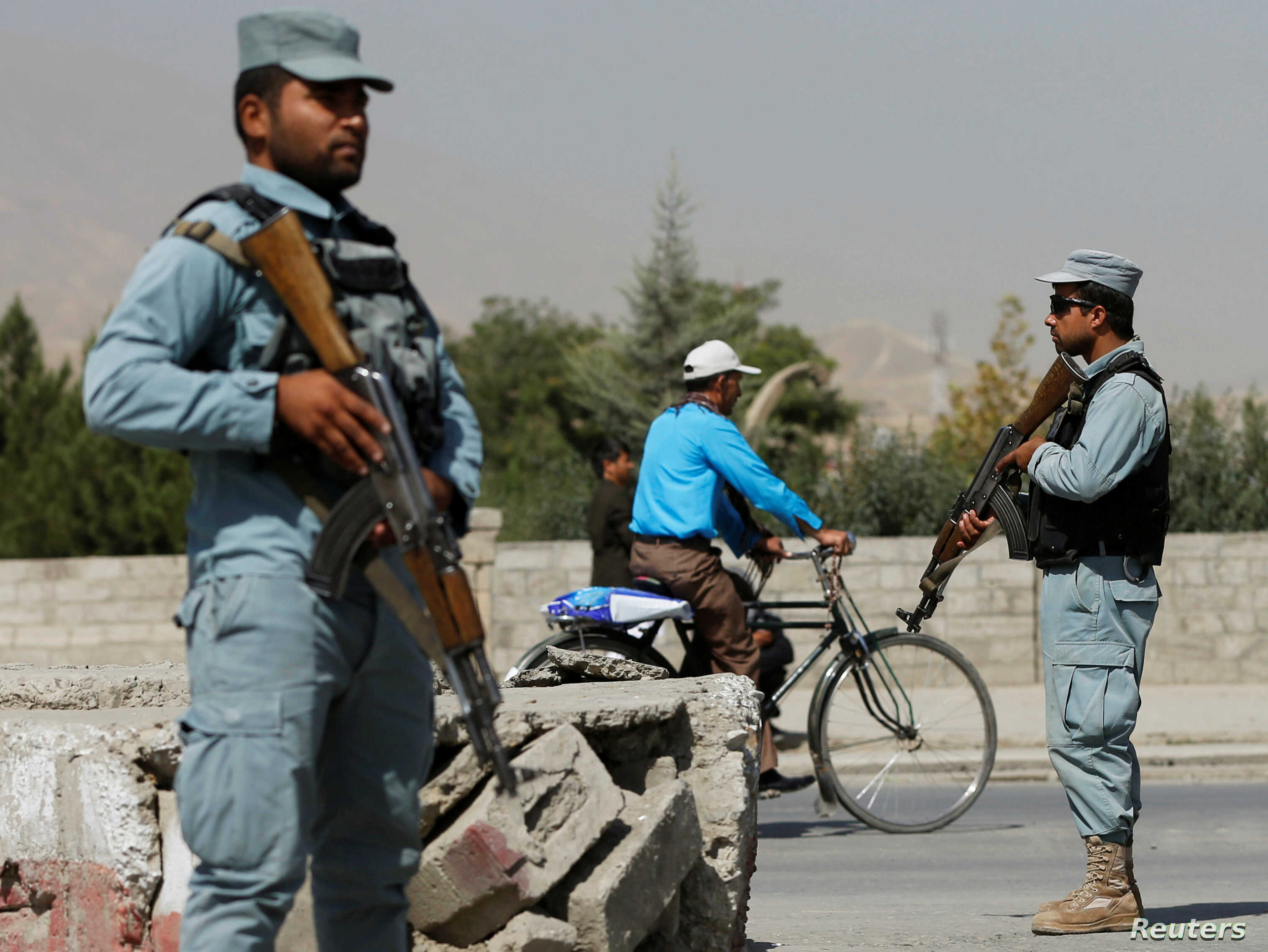 Afghan policemen stand guard at a checkpoint near the site of kidnapping in Kabul