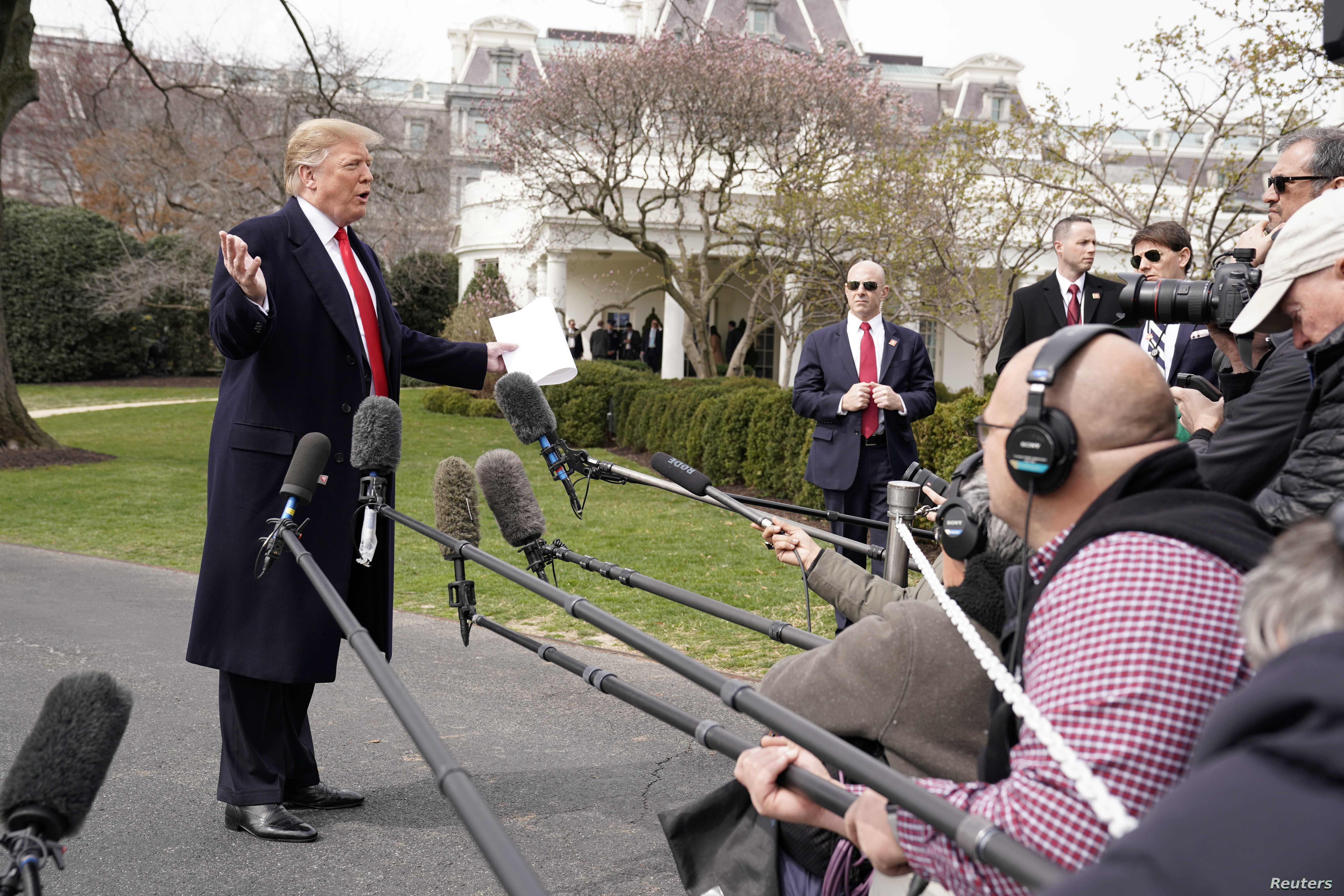 President Donald Trump talks to reporters as he departs on travel to Ohio from the White House in Washington, March 20, 2019.