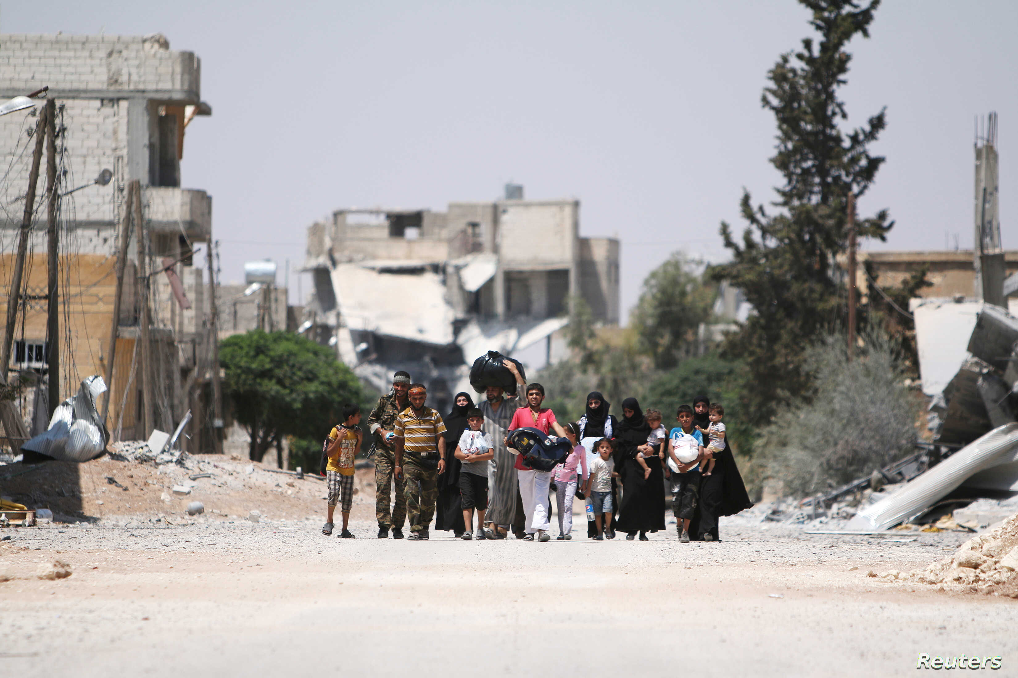 Syria Democratic Forces (SDF) fighters walk with people that fled their homes due to clashes between Islamic State fighters and Syria Democratic Forces (SDF) towards safer parts of Manbij, in Aleppo Governorate, Syria, August 7, 2016.