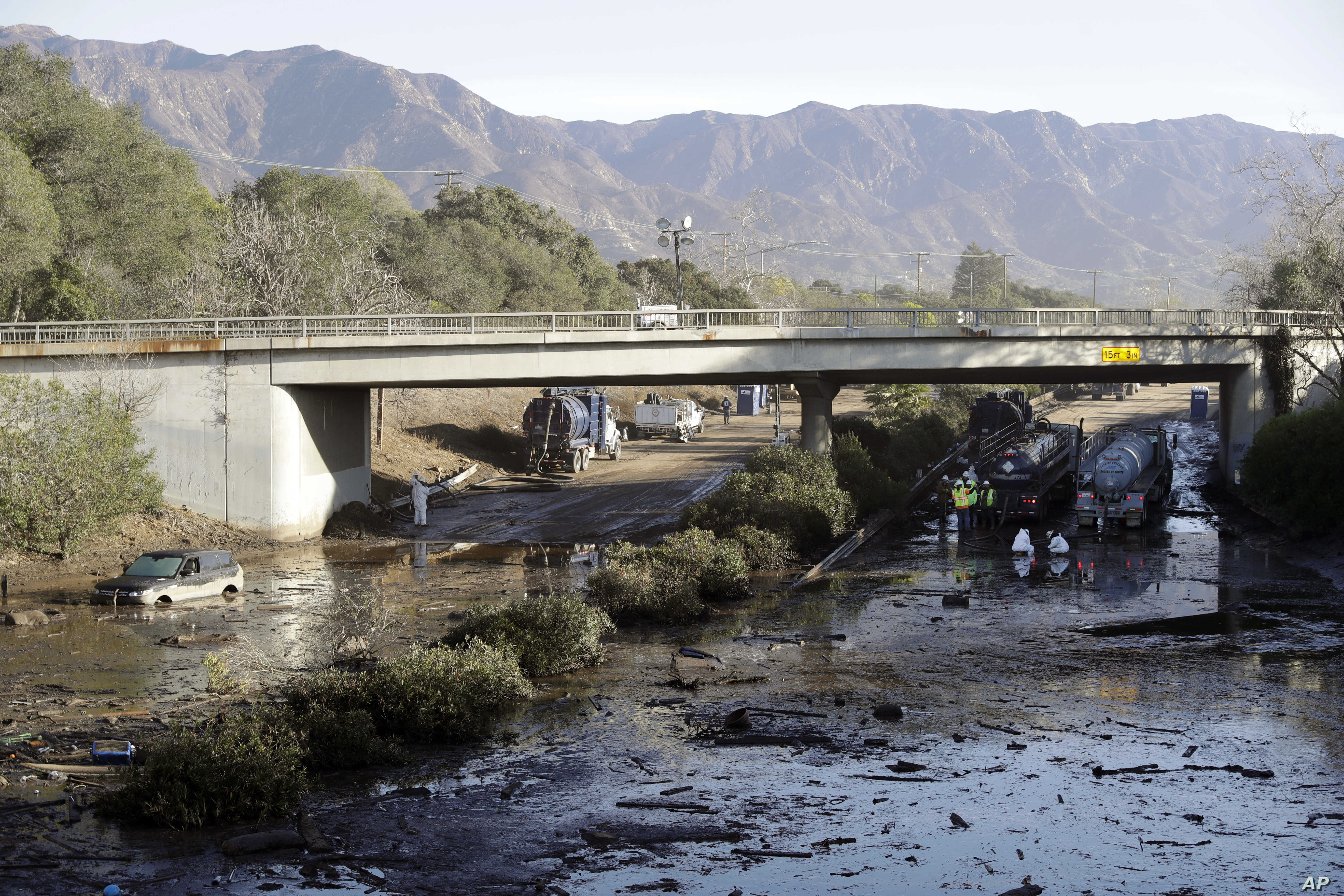 Crews work on clearing Highway 101 in the aftermath of a mudslide, Jan. 13, 2018, in Montecito, Calif. Most of the people of the town, usually known for its serenity and luxury, were under orders to stay out as gas and power were to be shut off Satur...