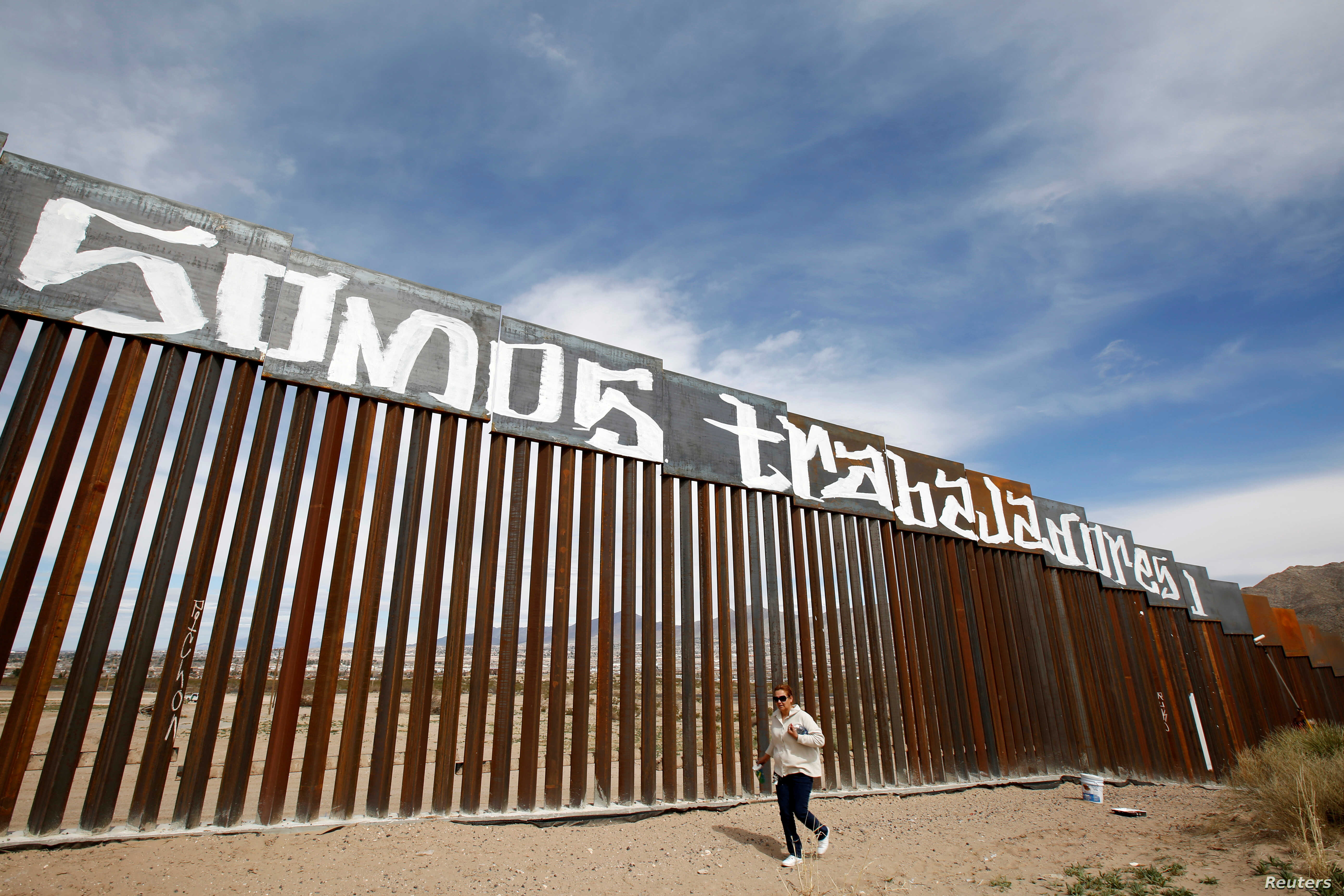 """A group of activists paints the U.S.-Mexico border wall between Ciudad Juarez and New Mexico as a symbol of protest against U.S. President Donald Trump's new immigration reform in Ciudad Juarez, Mexico, Feb. 26, 2017. The paint reads """"We are workers...."""