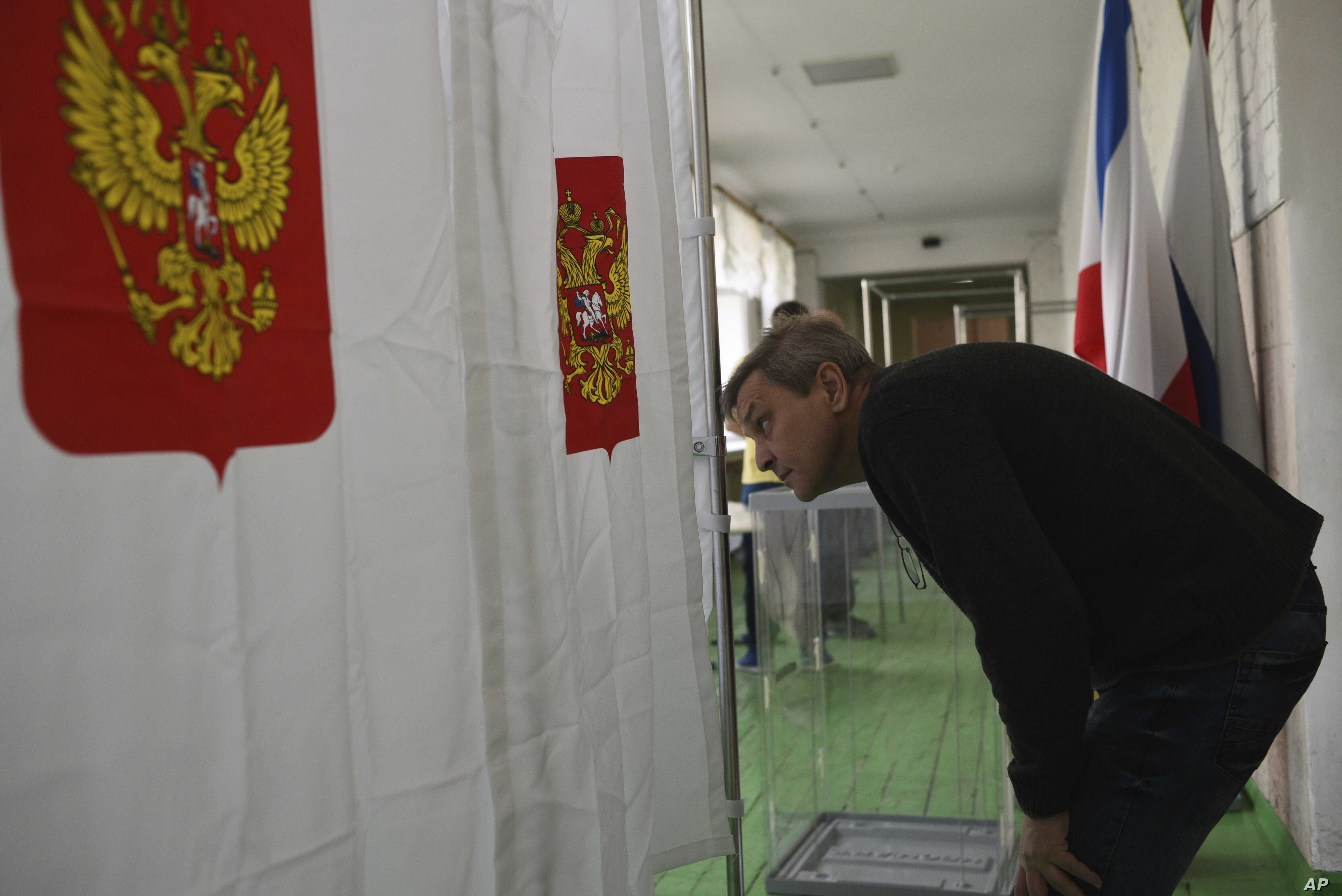 A polling station official checks vote cabins for the 2018 Russian presidential election in Simferopol, Crimea, March 17, 2018.