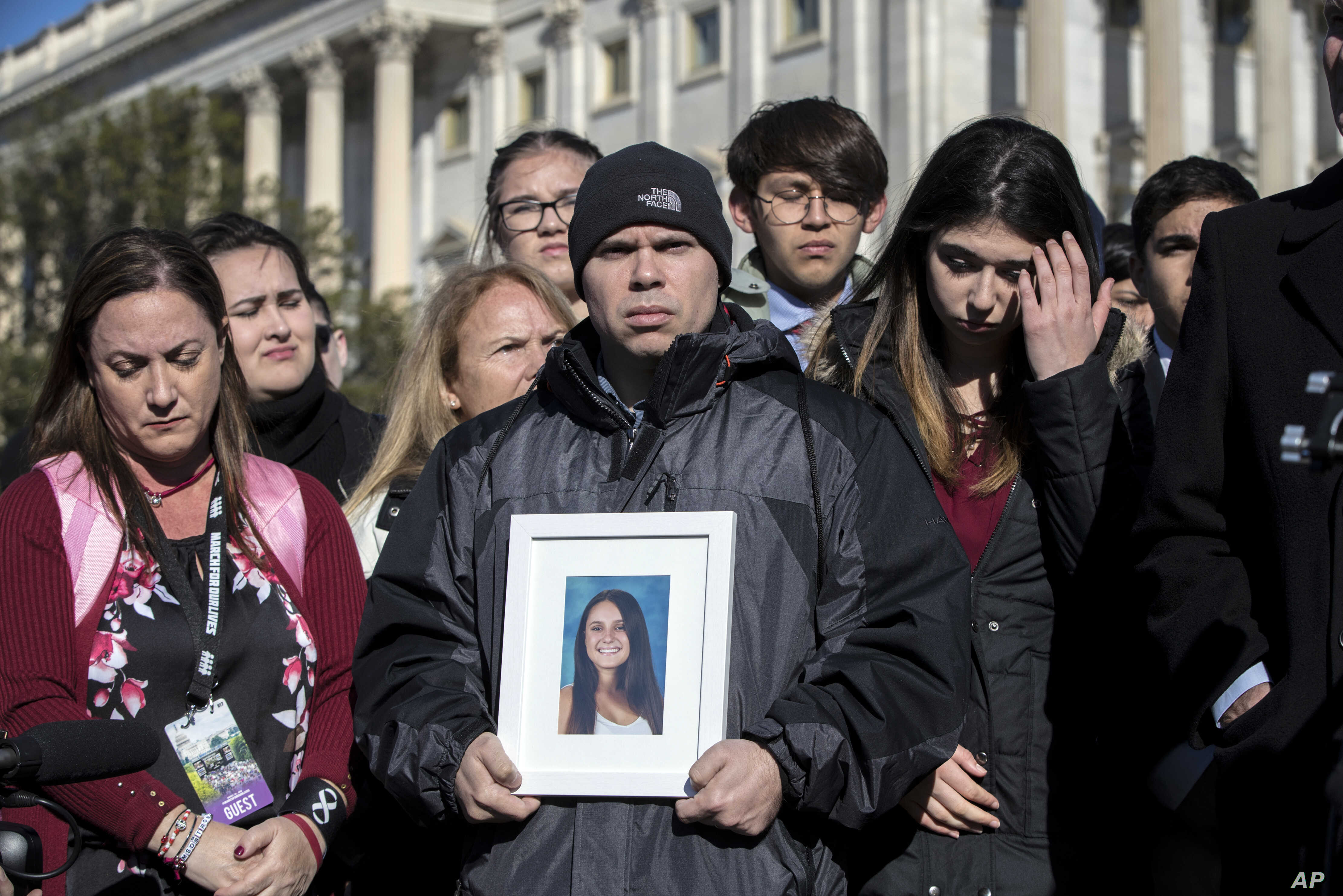 Ilan Alhadeff, joined at left by his wife, Lori, holds a photograph of their daughter, Alyssa Alhadeff, 14, who was killed at Marjory Stoneman Douglas High School in Parkland, Fla., during a rally by lawmakers and student activists in support of gun ...