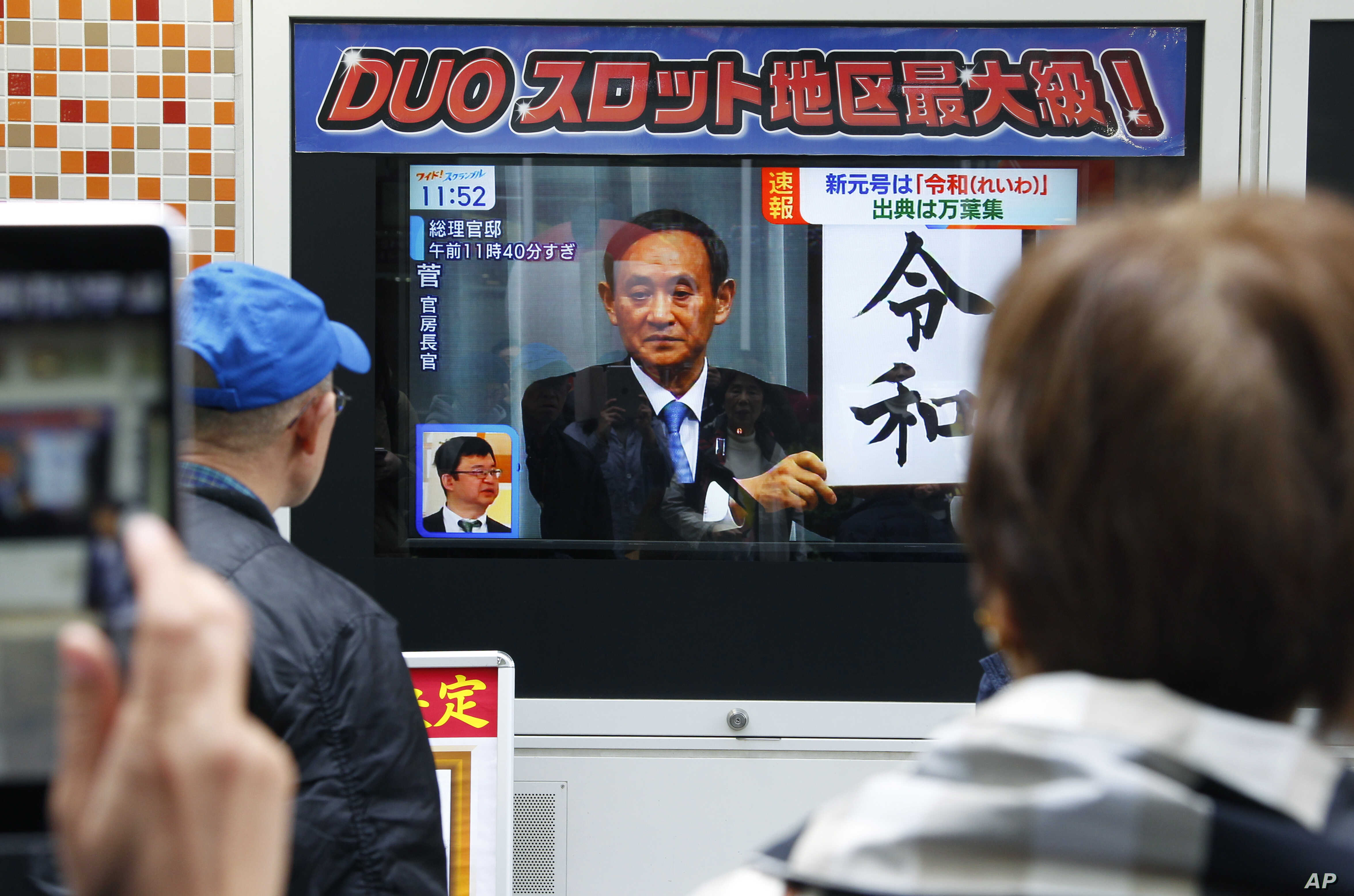 "People watch a TV screen showing the name of new era ""Reiwa"" is unveiled in a news program in Tokyo, Monday, April 1, 2019."