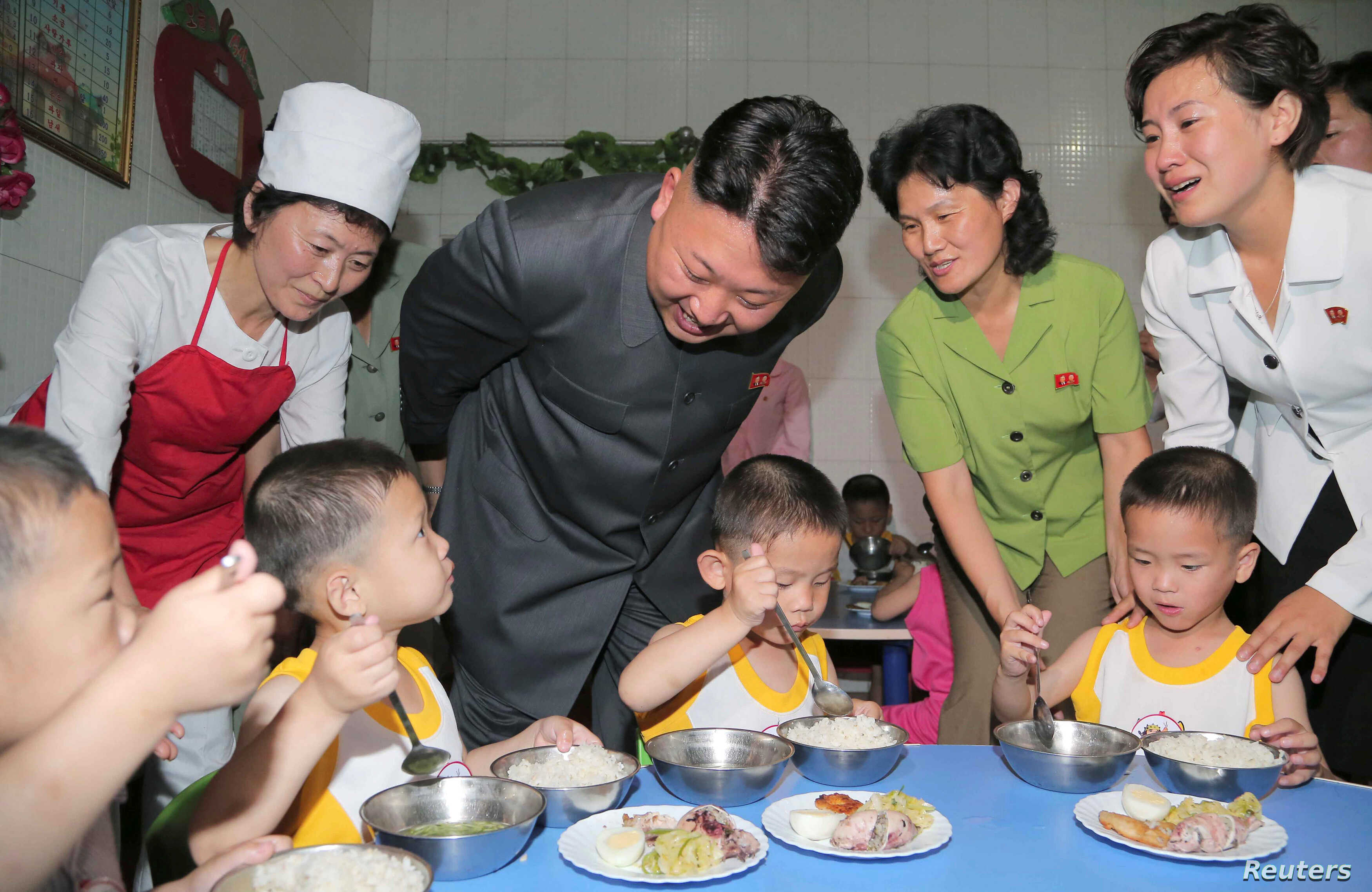 FILE PHOTO: North Korean leader Kim Jong Un smiles as children eat during his visit to the Pyongyang Orphanage on International Children's Day in this undated photo,  June 2, 2014.