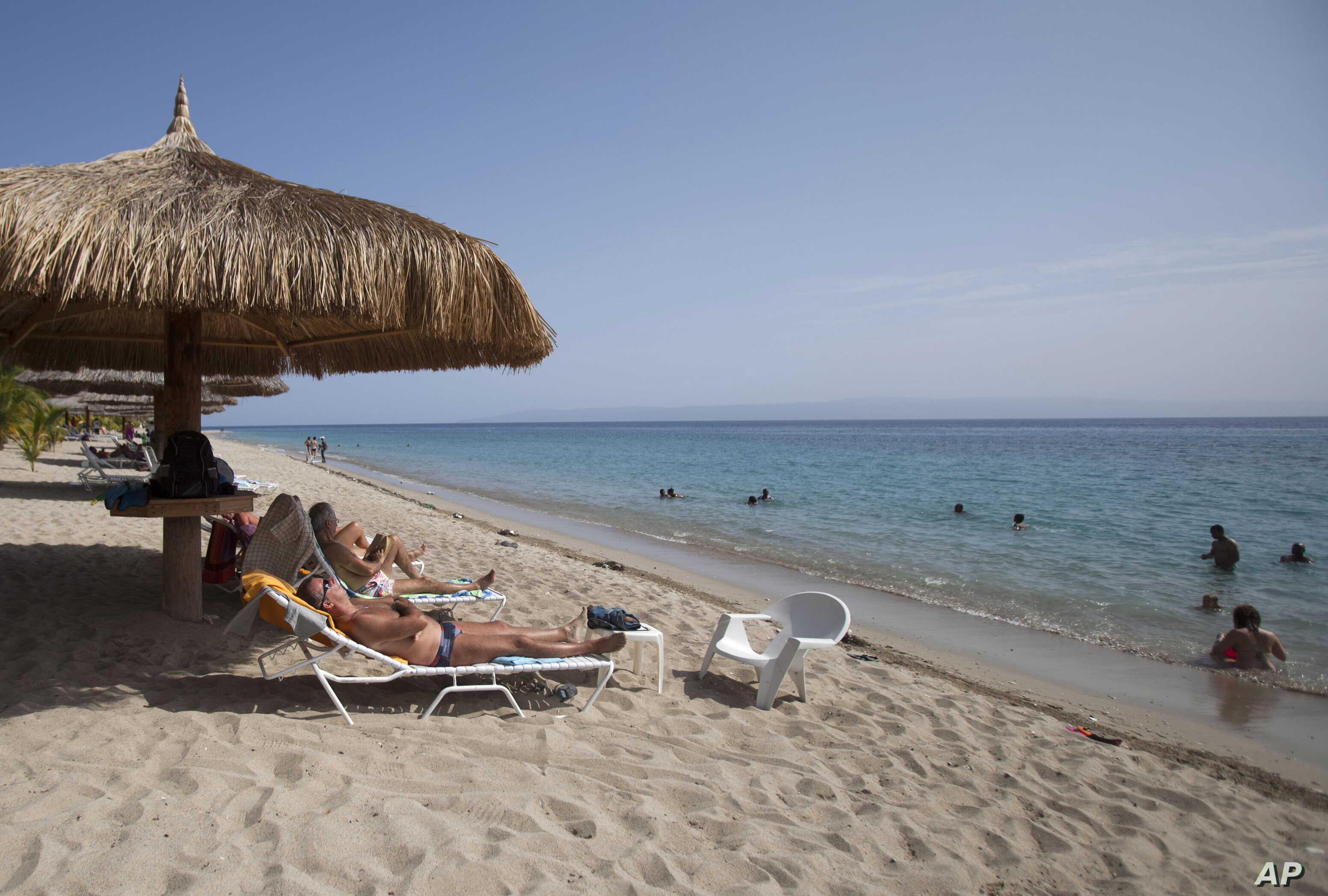 FILE - tourists rest seaside while others wade in the ocean waters at the Club Indigo beach resort in Montrouis, Haiti.