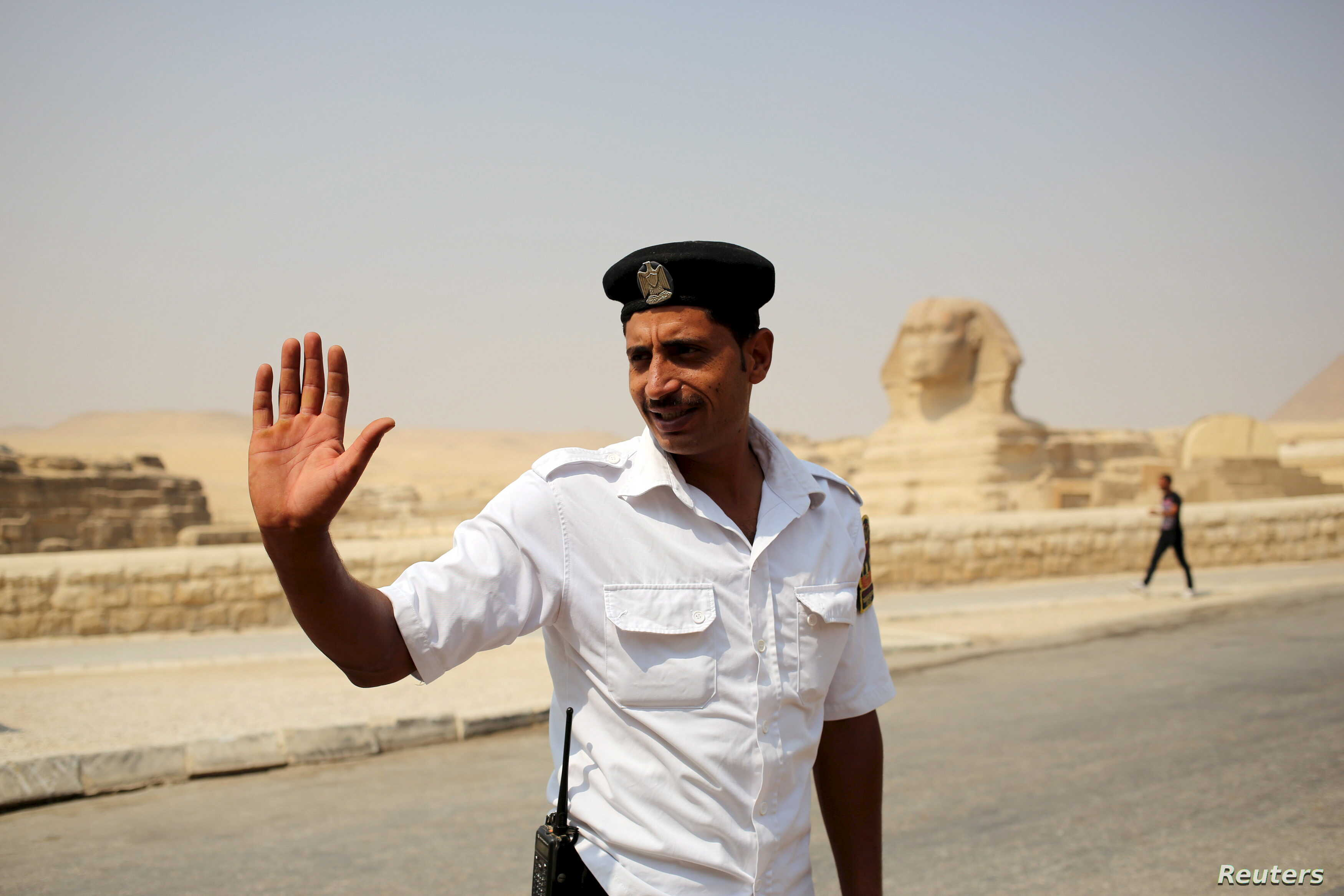 FILE - A policeman gestures to people as he stands guard near the Sphinx, near the pyramids plateau, Egypt, June 11, 2015.