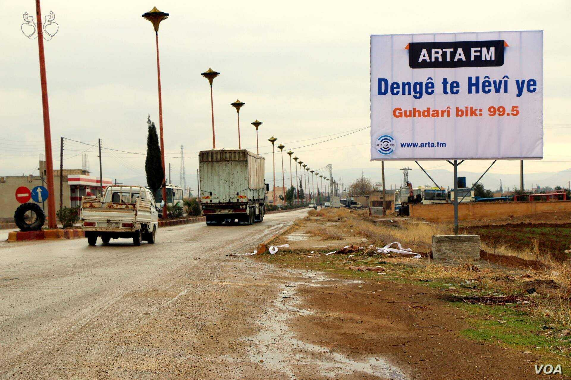 """A billboard reads """"Your voice is hope"""" at the entrance of Amude."""