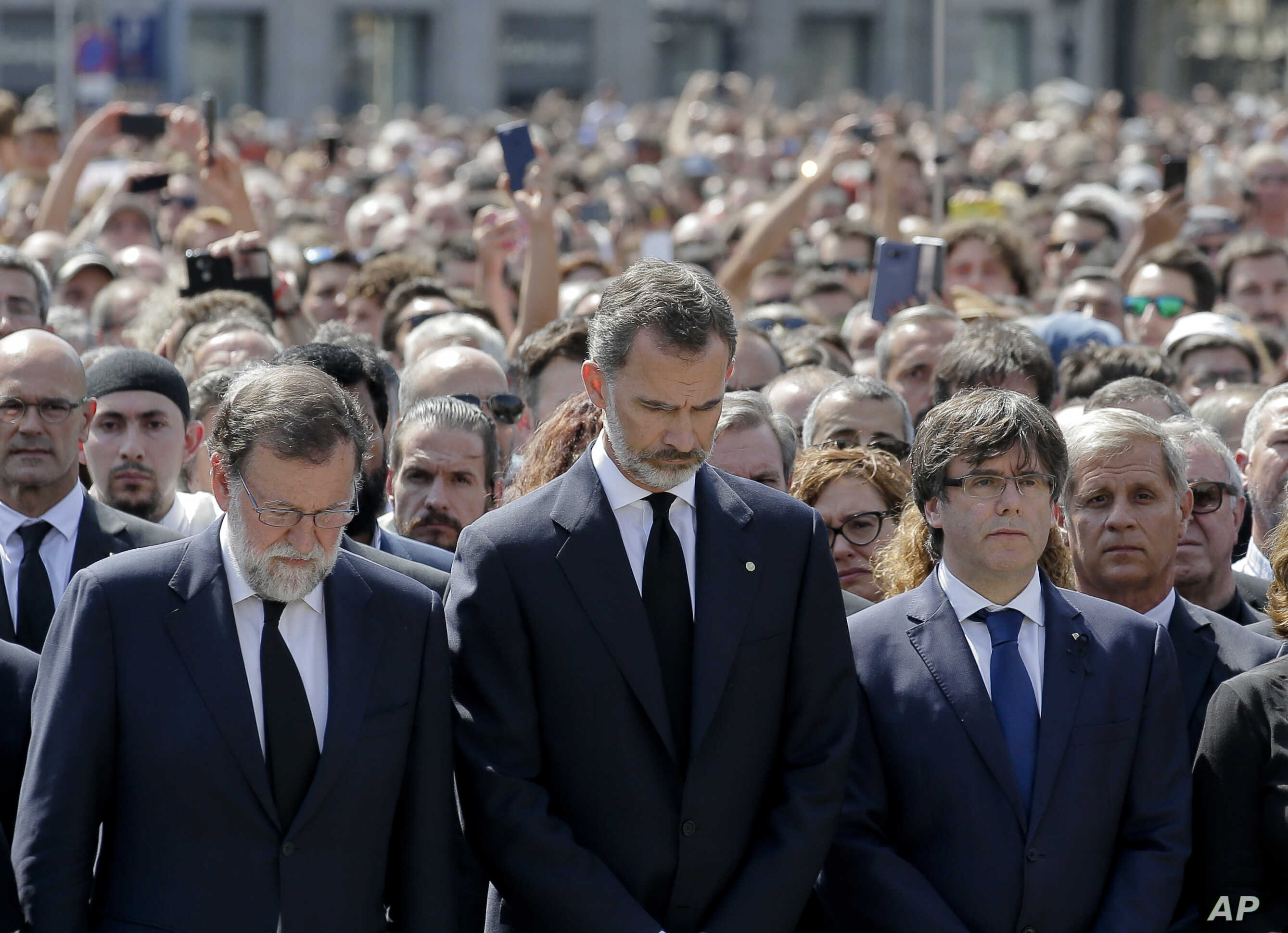 King Felipe of Spain, center, Prime Minister Mariano Rajoy, center left, and Catalonia regional President Carles Puigdemont, center right, join people gathered for a minute of silence in memory of the terrorist attacks victims in Las Ramblas, Barcelo...