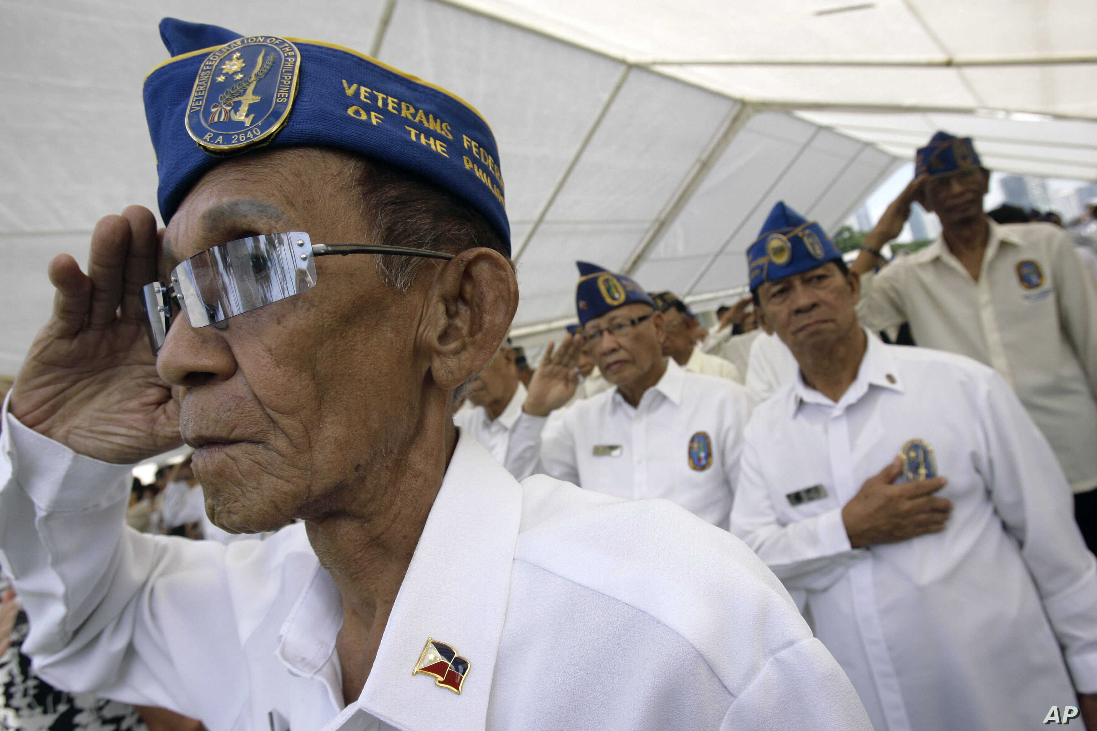 FILE - Filipino veterans salute during ceremonies for U.S. Memorial Day at the American Cemetery in suburban Taguig, south of Manila, Philippines, May 24, 2009.