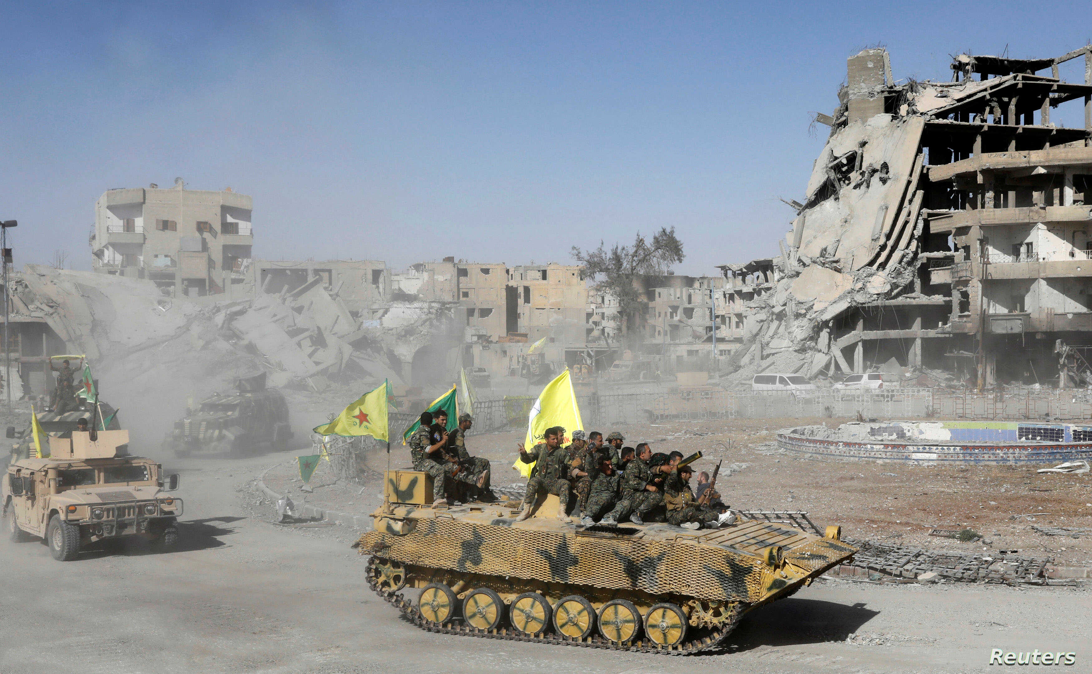 Syrian Democratic Forces (SDF) fighters ride atop of military vehicles as they celebrate victory in Raqqa, Syria, Oct. 17, 2017.
