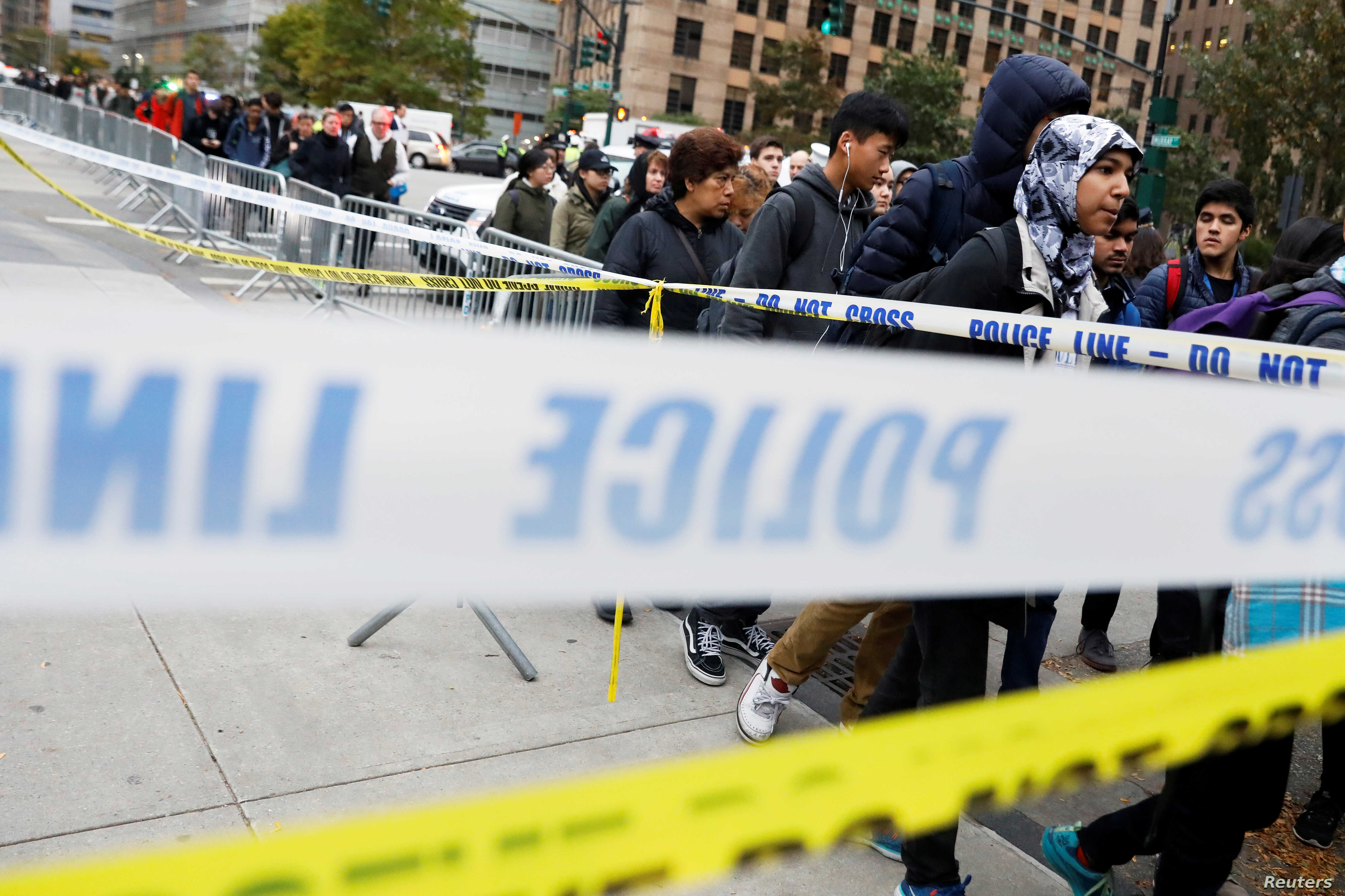 Students walk past police line tape on their way to school a day after a man driving a rented pickup truck mowed down pedestrians and cyclists on a bike path alongside the Hudson River in New York City, Nov. 1, 2017.