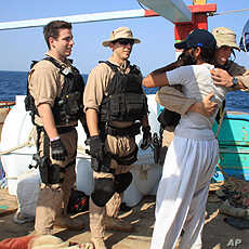 U.S. Navy sailors assigned to the guided-missile destroyer USS Kidd  greet a crew member of the Iranian fishing vessel, the Al Molai Friday, Jan. 6, 2012 in the Arabian Sea.