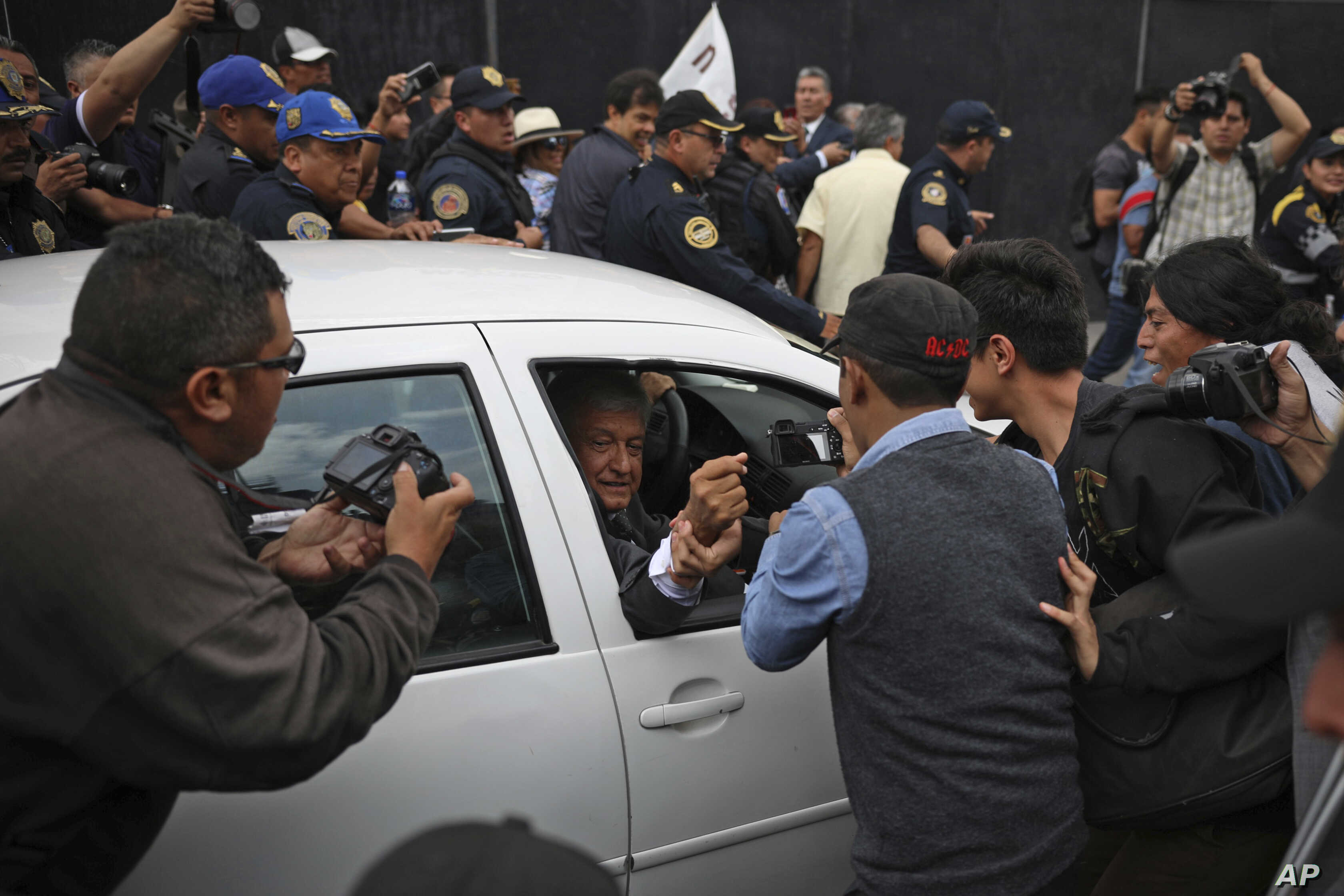 Mexico's President-elect Andres Manuel Lopez Obrador greets a supporter as he leaves the National Palace where he met with Mexico's President Enrique Pena Nieto in Mexico City, July 3, 2018.