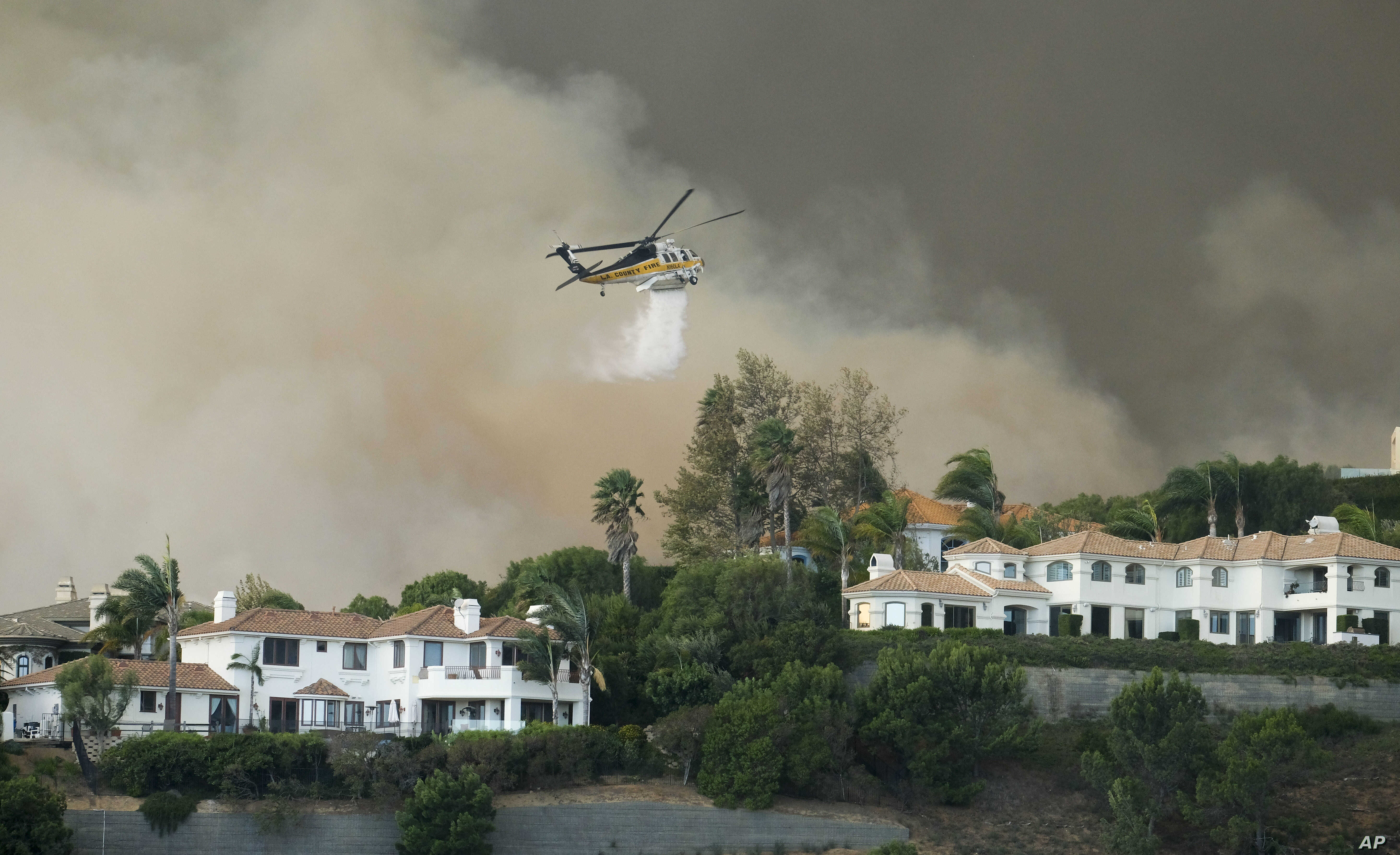 A helicopter drops water on a brush fire behind homes during the Woolsey Fire in Malibu, Calif., Nov. 9, 2018. A fast-moving wildfire in Southern California has scorched a historic movie site and forced numerous celebrities to join the thousands flee...